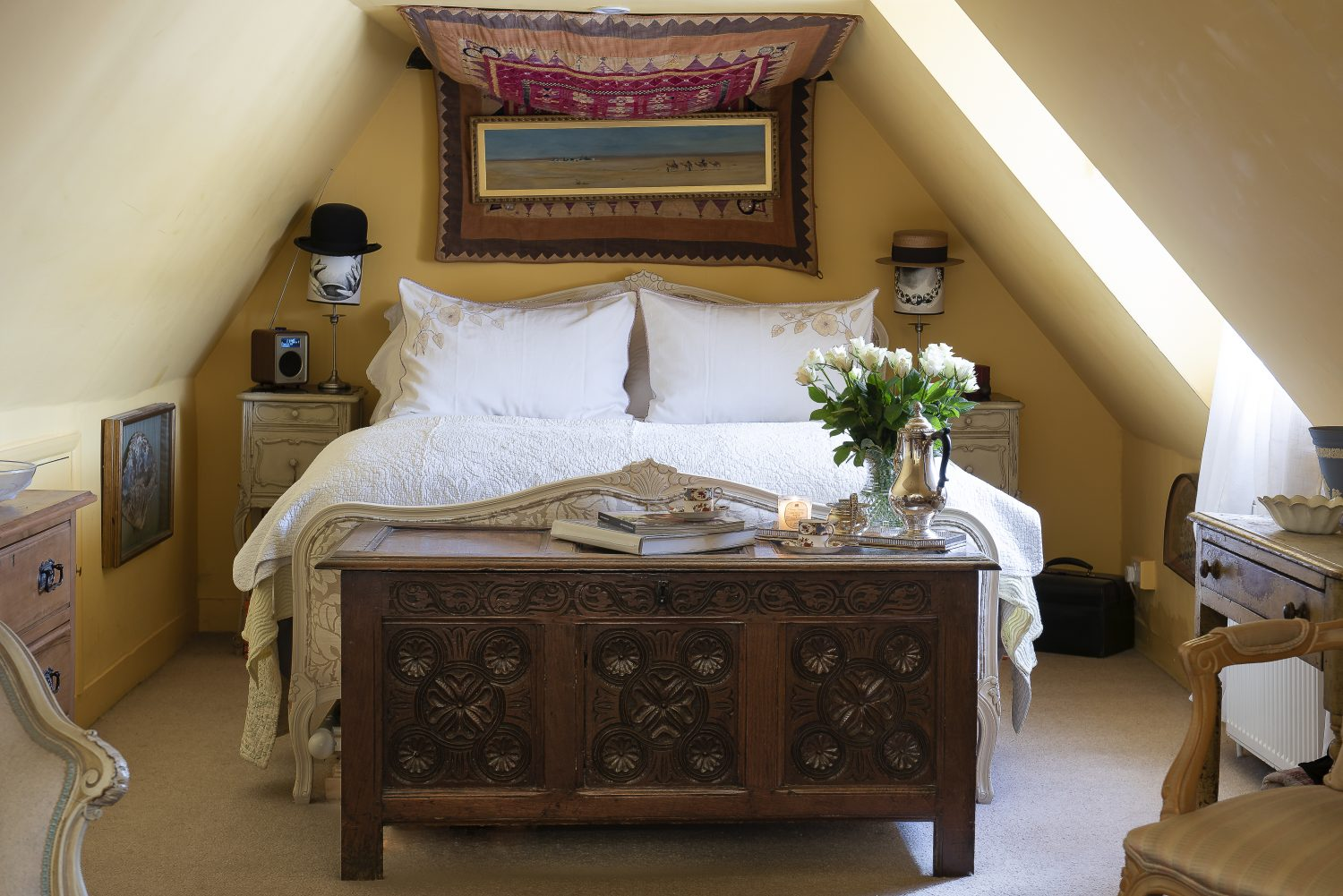 The Fornasetti lamp shades in the master bedroom are topped with vintage hats. The tapestry over the bed is an antique ceremonial Indian bullock blanket