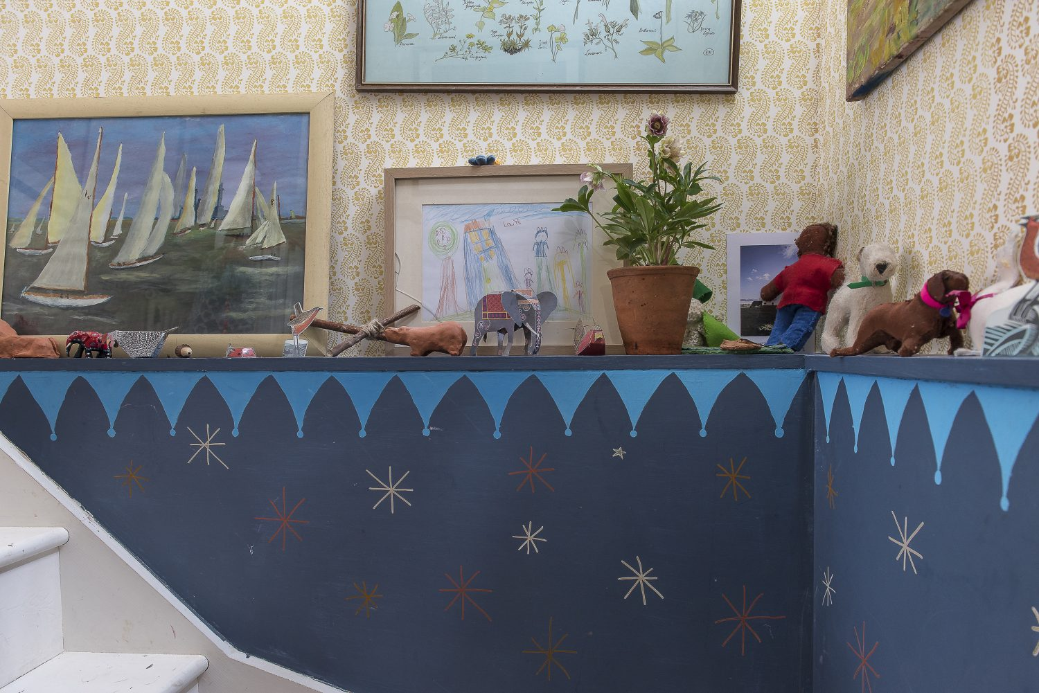 Molly and the children painted the stars on to the blue paint on the staircase walls. The wallpaper is Molly's Lani design