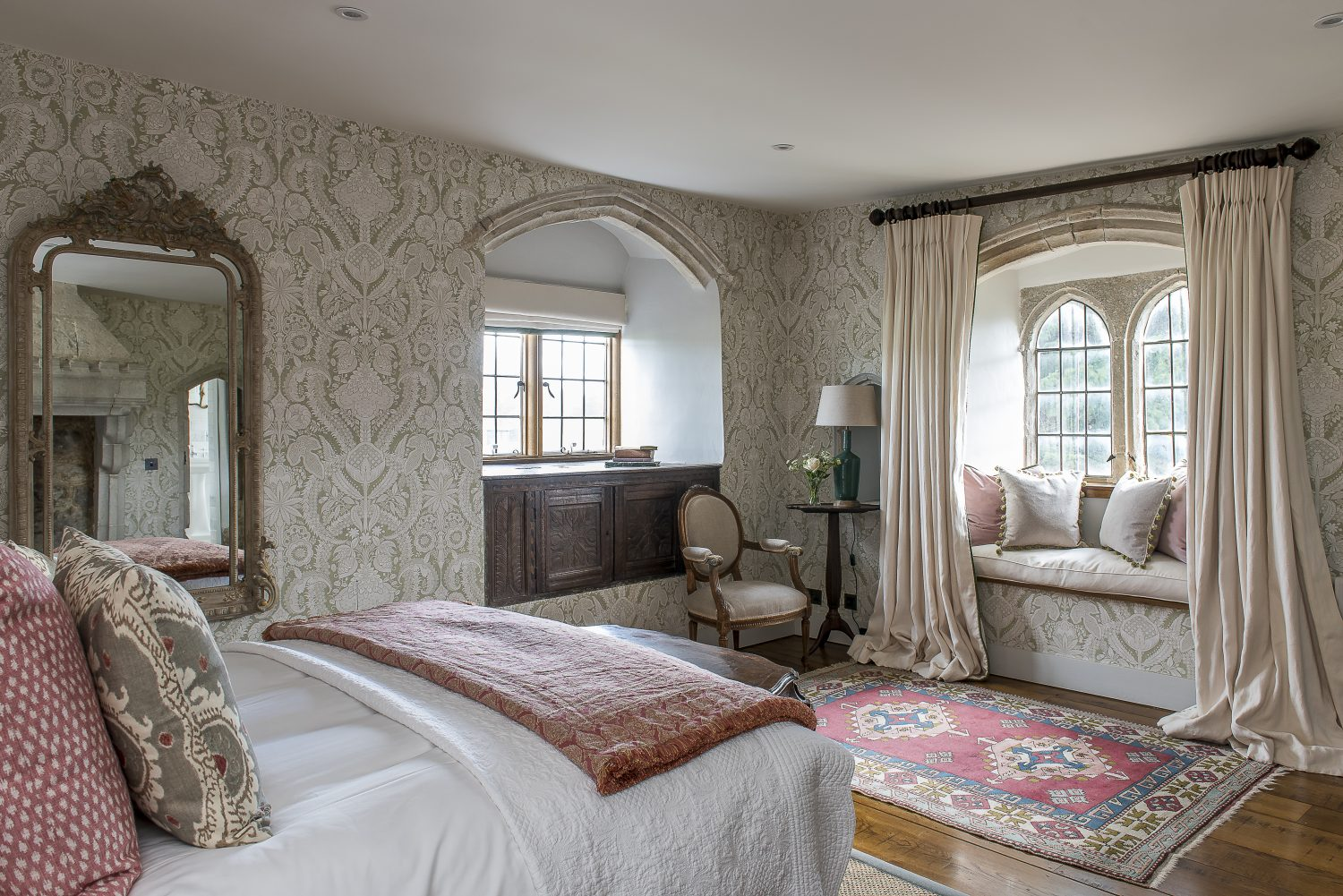 Arched stone windows and puddled curtains in the Hellebore bedroom