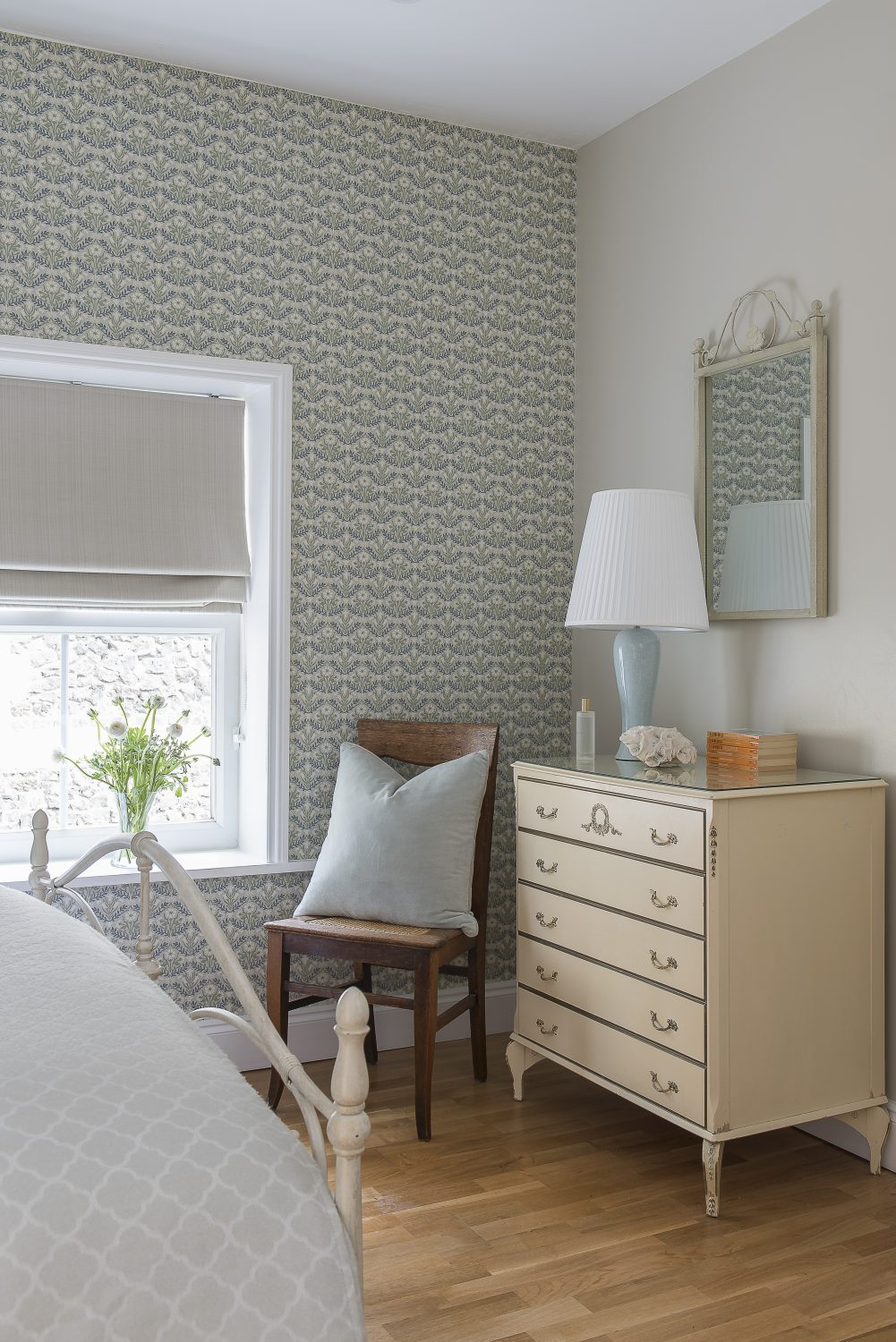 The sixth bedroom is referred to as the 'French Room', with a 1960s Louis Fooey chest of drawers and pretty, patterned wallpaper