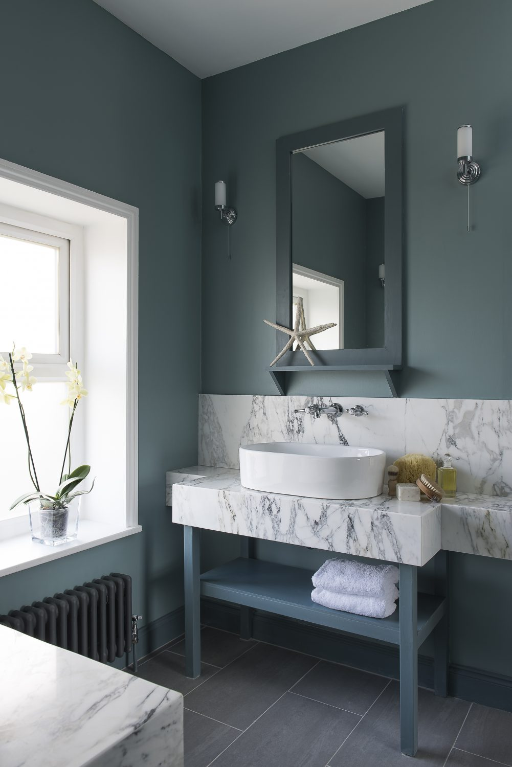 A beautiful petrol-blue bathroom has opposing counter-top basins