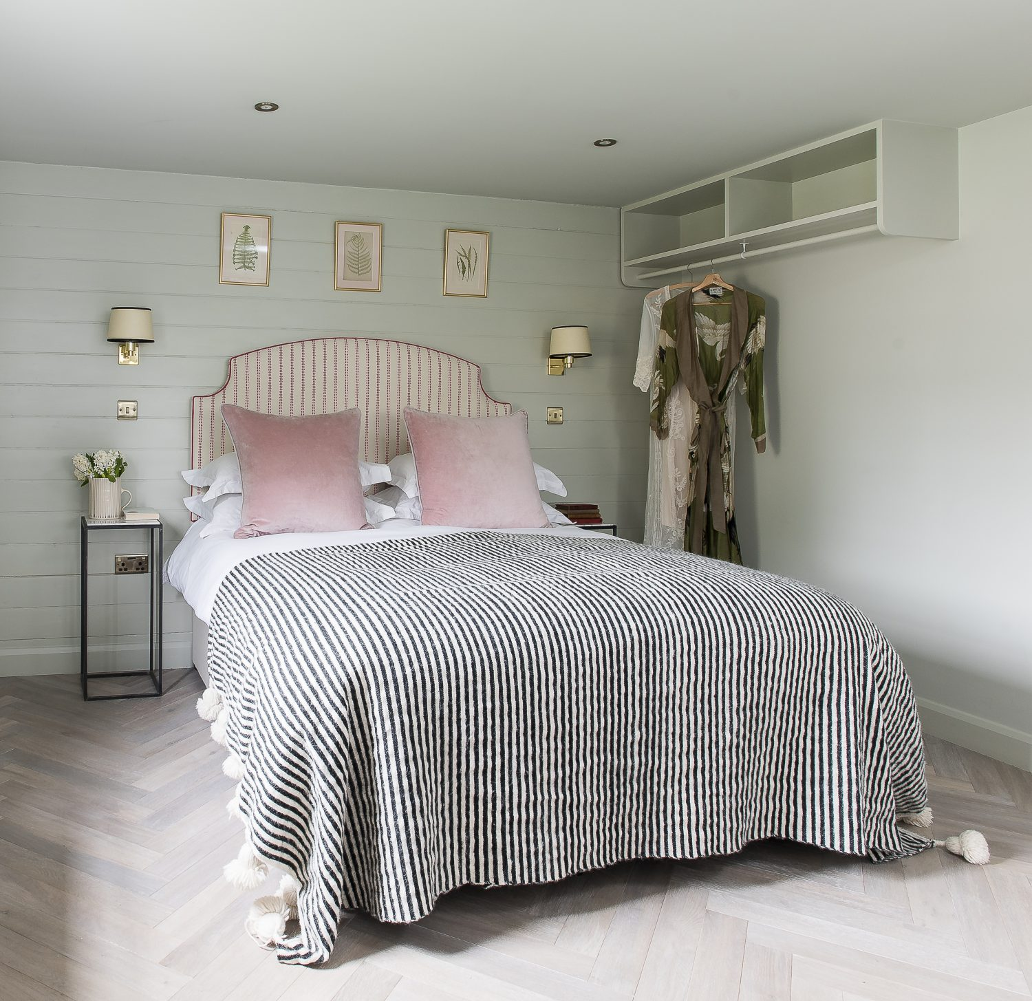 In the main bedroom, a pink and white striped headboard from The Headboard Workshop is upholstered in fabric by Vanessa Arbuthnot