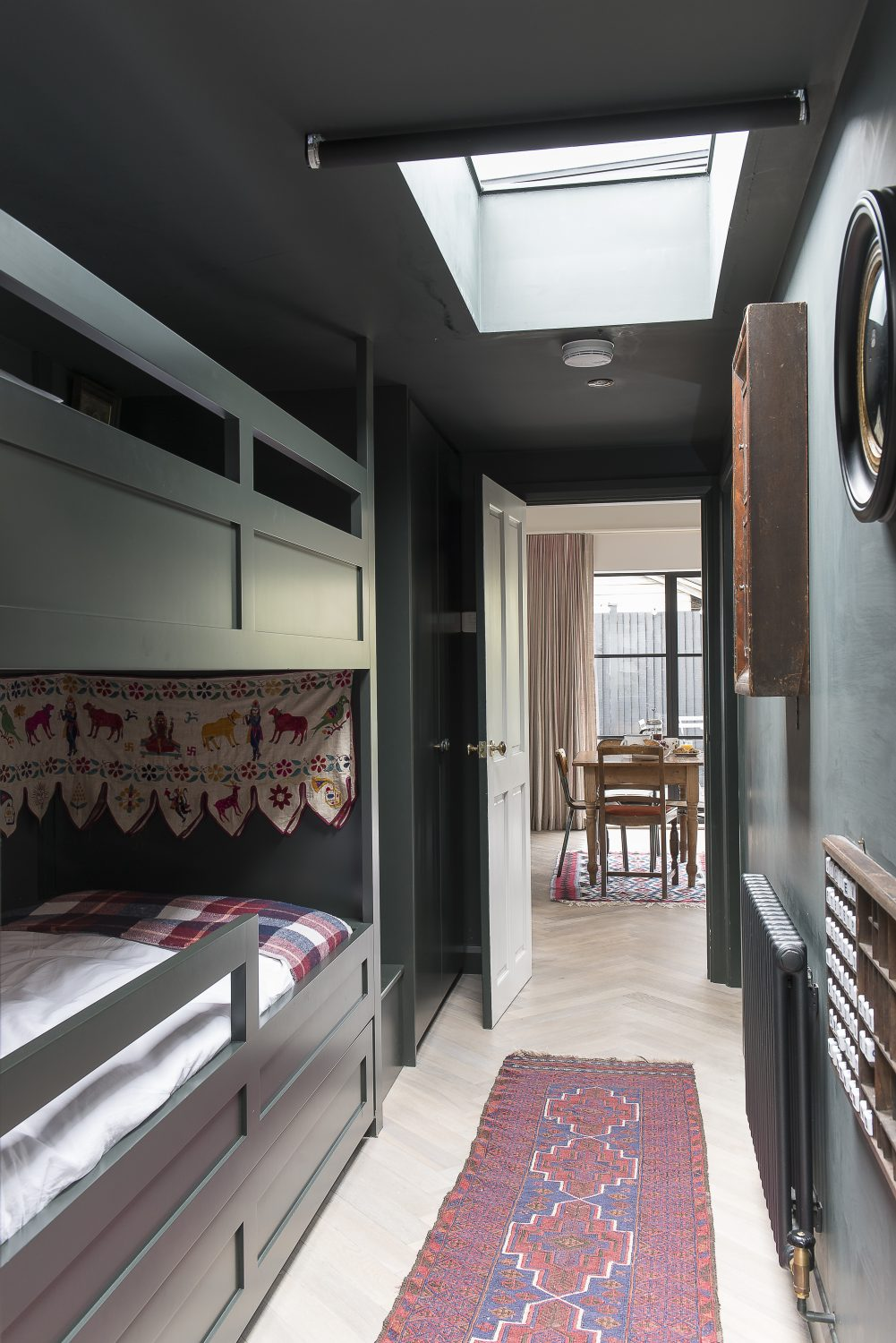 The second bedroom, with two built-in bunk beds, is painted a deep green. Guests often leave messages in an old printer's tray, into which Amy has put some letter cubes