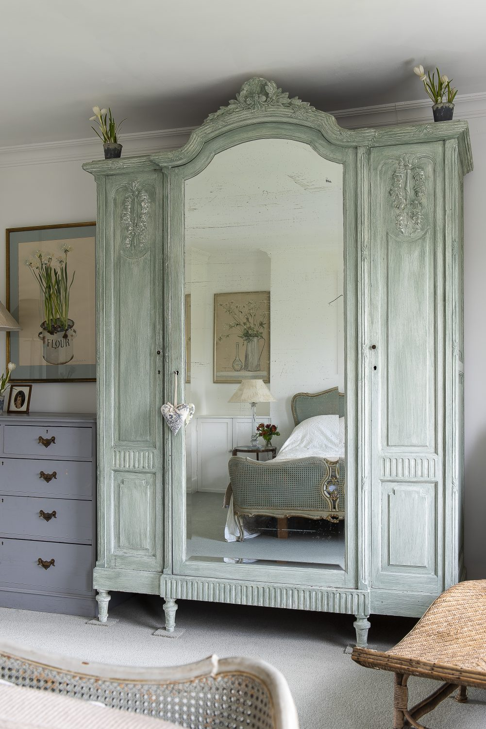 "The bed in the spare room was bought from a French brocante for £20, and the ""smudgy green"" wardrobe was found at 'Tasha Interiors. On one wall two swifts chase a butterfly, painted by the owner"