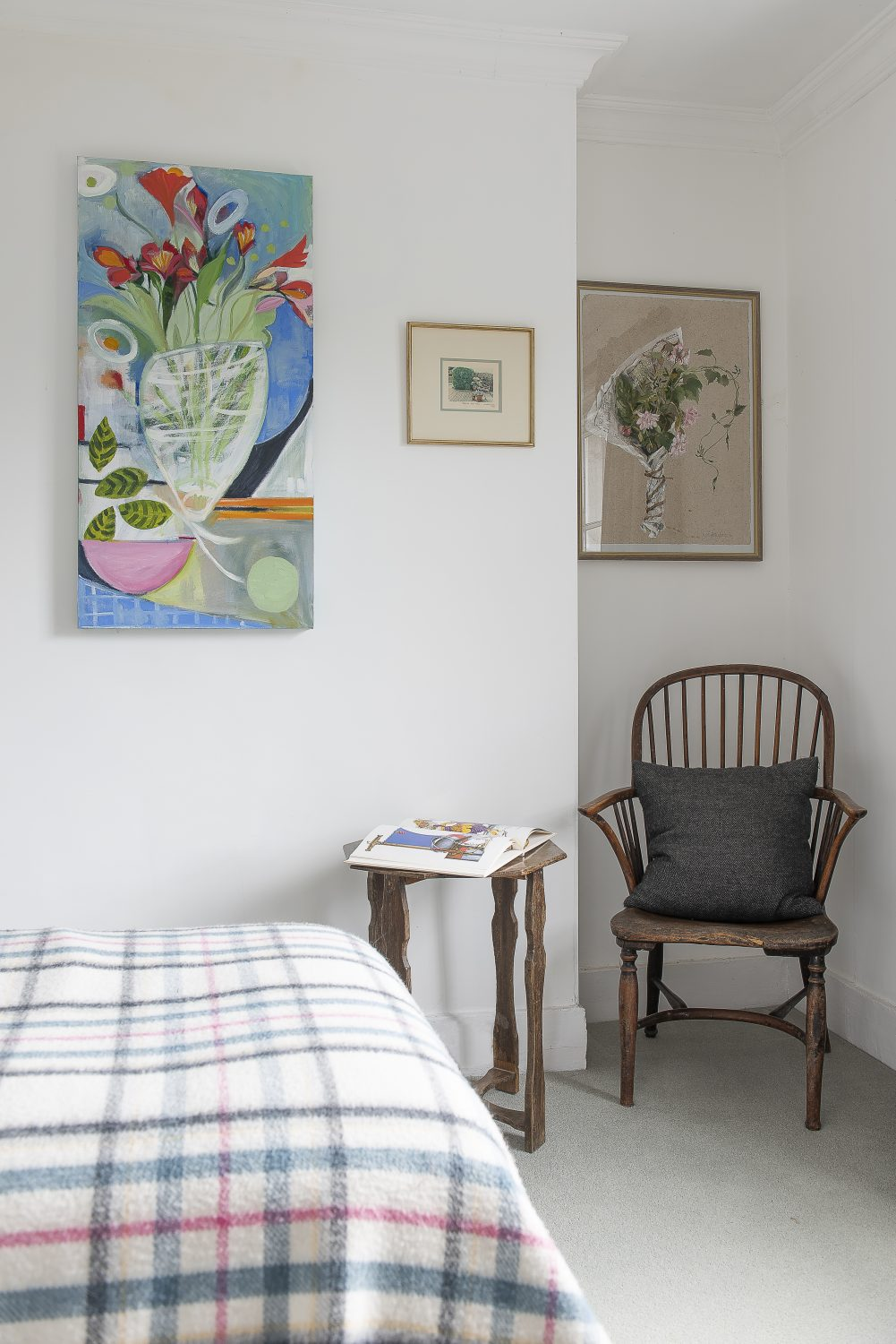 In contrast to the cool white walls in a small guest bedroom, colourful floral abstract paintings provide a splash of primary colour