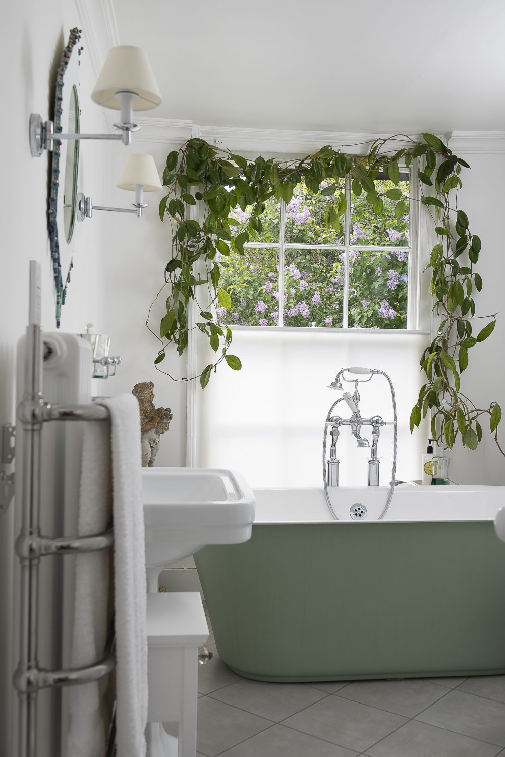 As you enter the upstairs bathroom, a wonderful hoya plant frames the large window above the sage green roll-top bath and gives a view out to a lilac tree in full bloom.