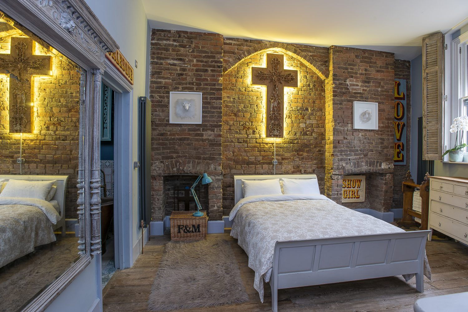 A backlit crucifix provides a stunning focal point in the guest bedroom and alludes to The Bath House's former use as a church