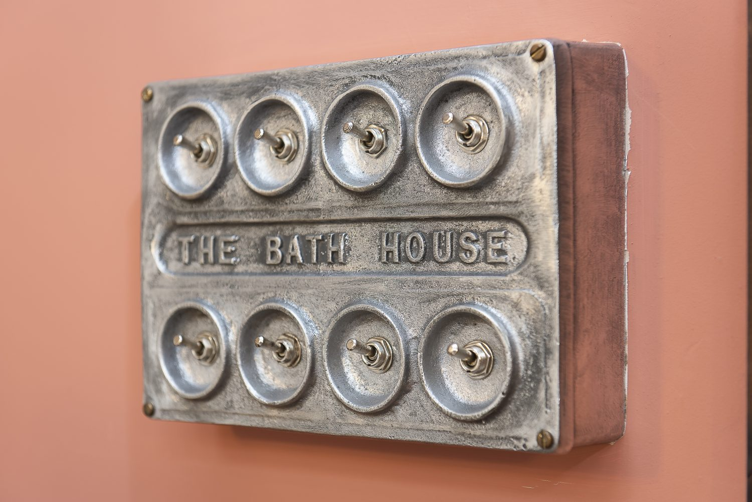 Bespoke industrial steel light switches and plug points are embossed with the words The Bath House