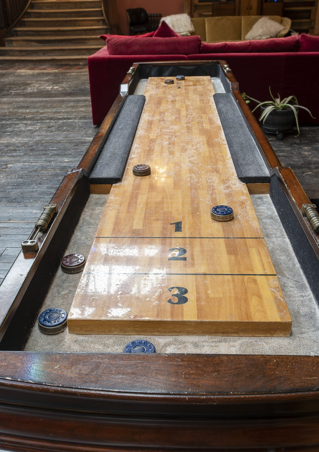 The living space is filled with original finds, such as this vintage shuffleboard table