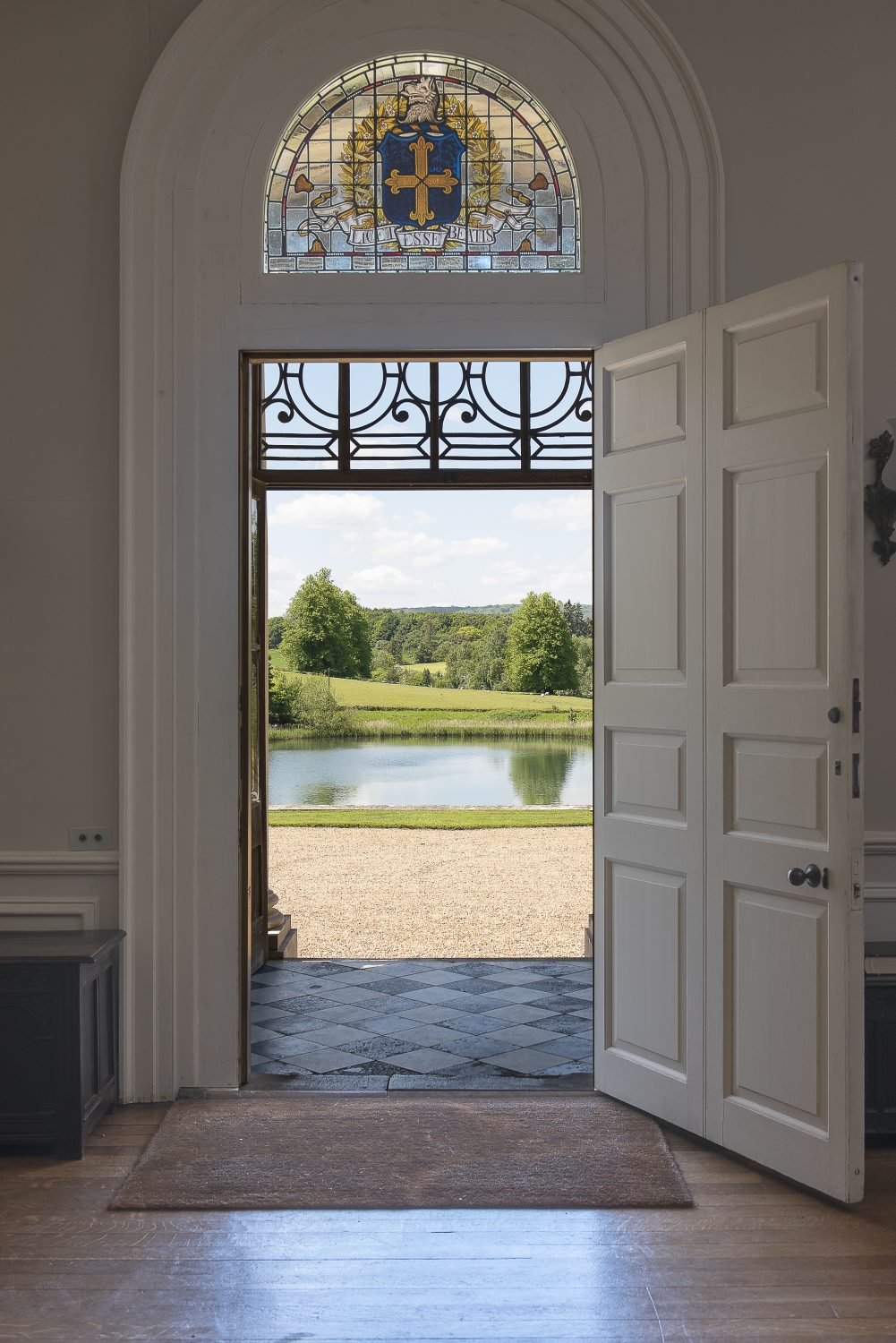 Beautiful views over the lake to the west of Squerryes. The family motto immortalised in stained glass Below: The formal back garden was designed by Henry's mother Anthea to a more formal design she found on old plans