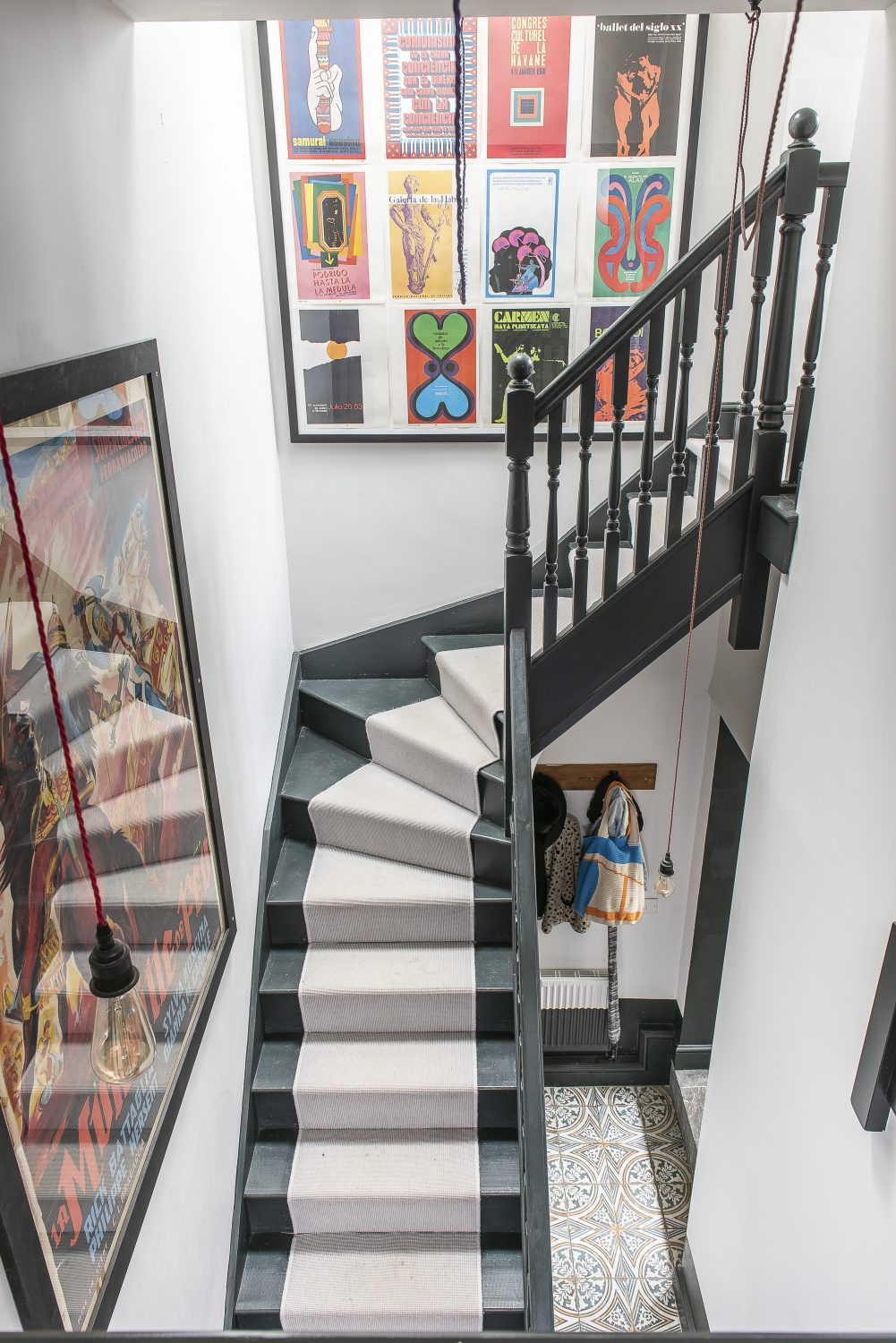 The lofty stairwell opens up to a gallery on the first floor, where more coloured cables from Dyke & Dean are strung across the void. Two extra large frames, one containing an old film poster, the other a collage of Cuban posters from a book, hang on the walls