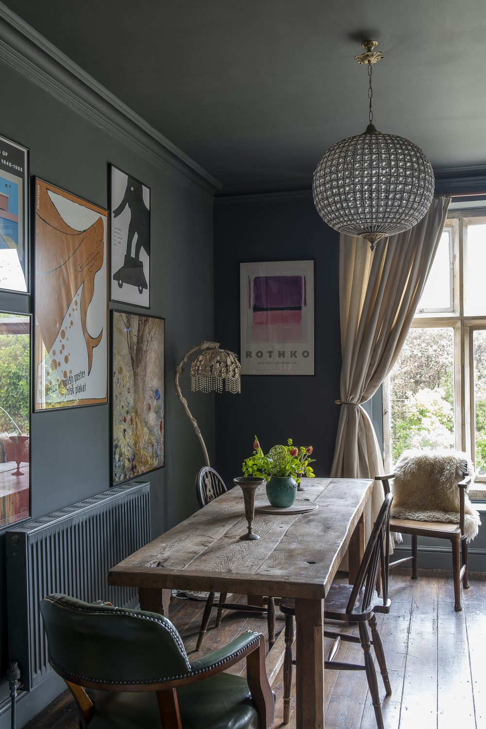 A cosy sitting room, used as a games room, features the original Delft tiles around the fireplace and stone-mullioned windows; opposite the fireplace, a refectory table provides the perfect place to set up a Monopoly board