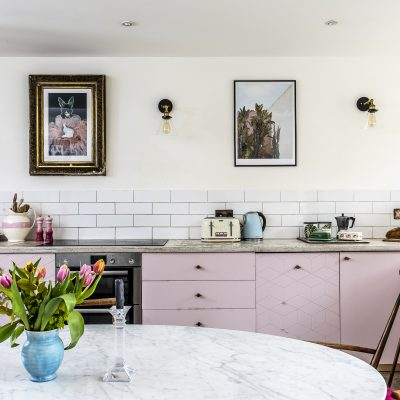 The working part of the kitchen is confined to one wall with cupboards painted a dusty pink, some with a geometric pattern in copper. The worktop is poured concrete and the wall lights are from eBay