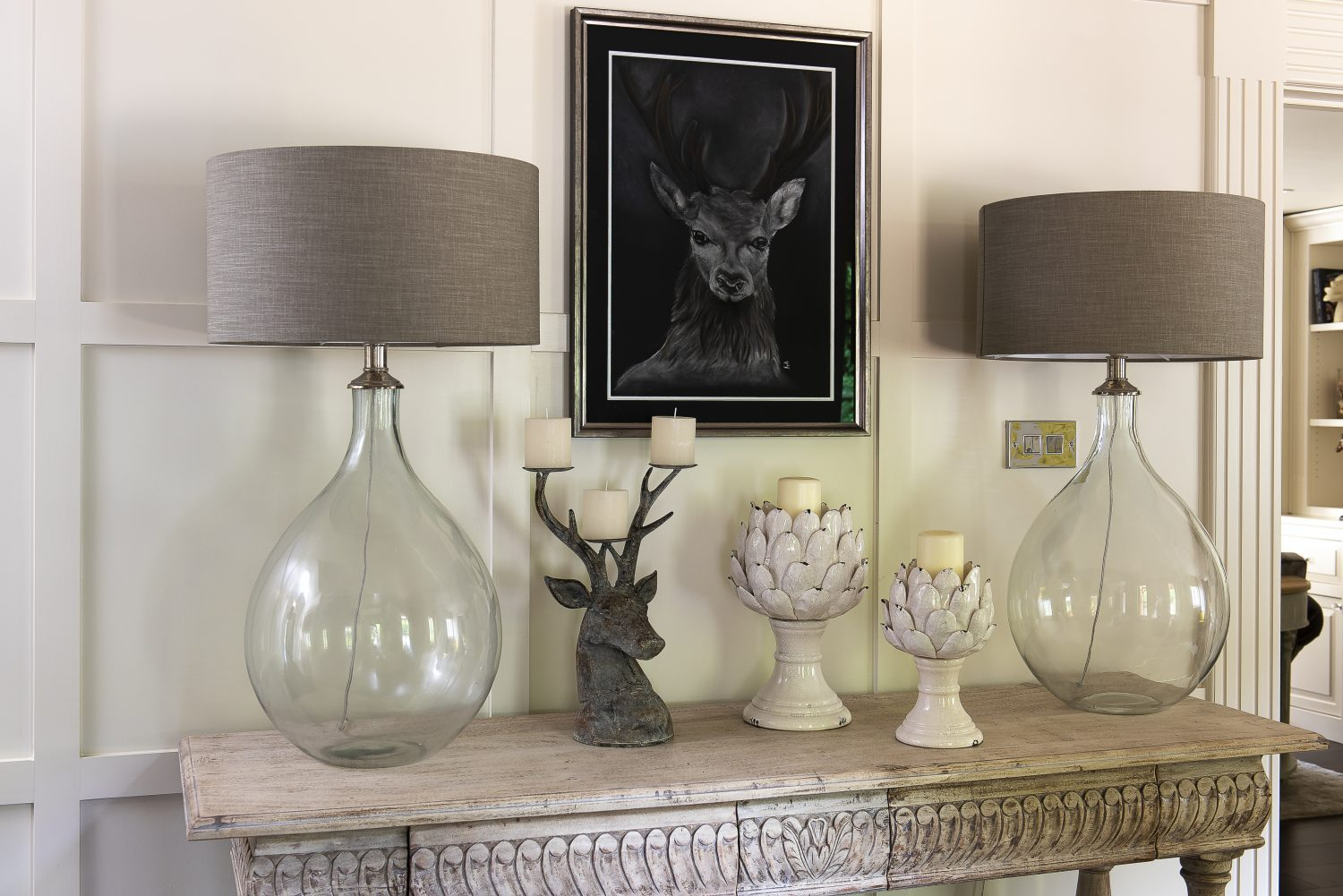 One of Karen's many animal paintings hangs above the hall table. The lamps are from OKA and the stag candelabra from one of her favourite shops, Flowerhouse and Hom
