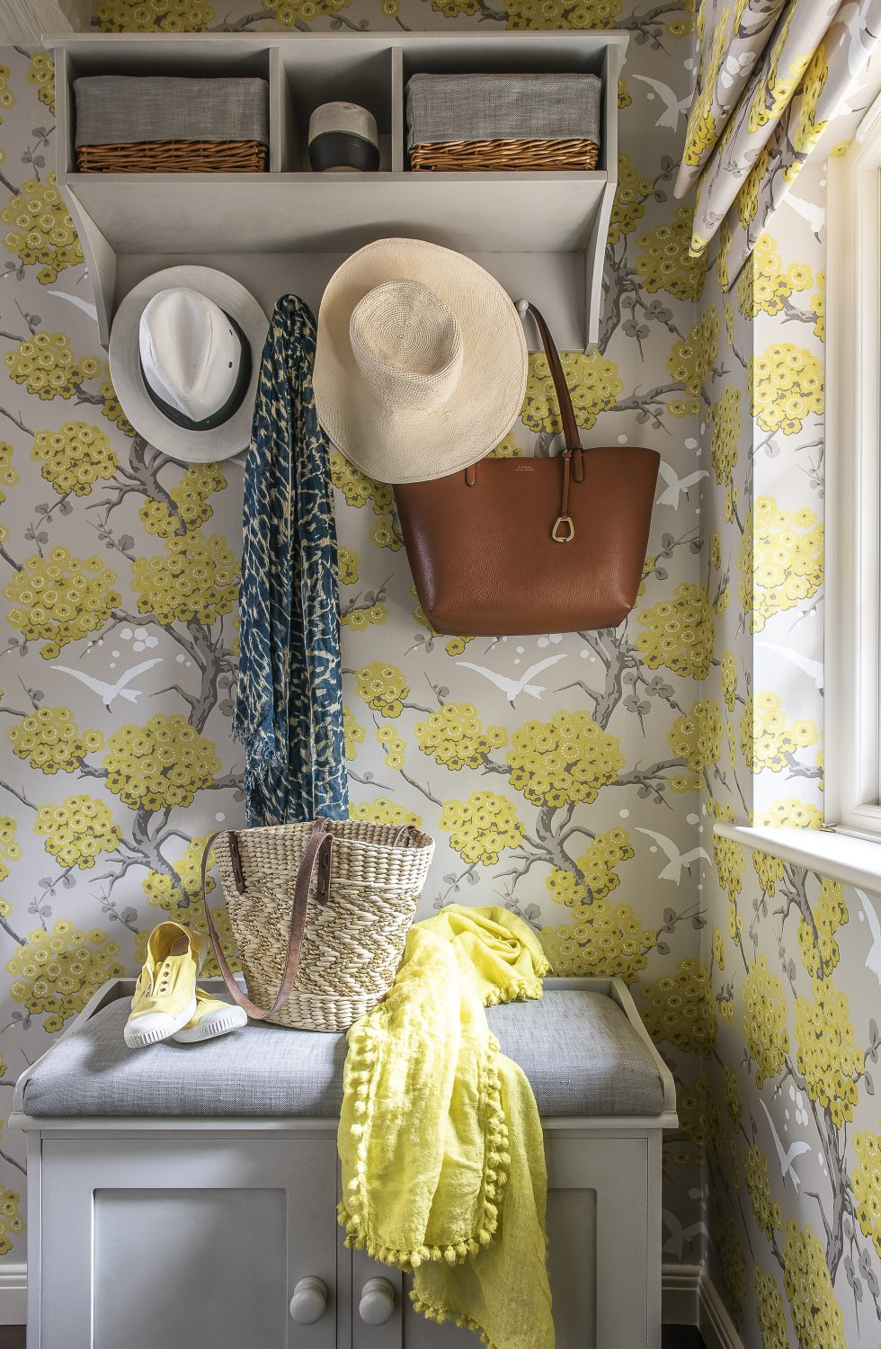 The hall is a mix of soft grey panelling and citrus yellow floral wallpaper from Osborne & Little