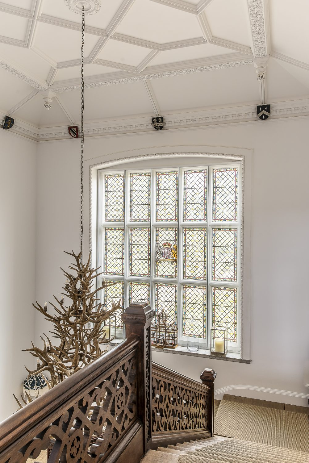 An enormous antler chandelier hangs down from the ceiling, whilst vibrant artworks and soft furnishing contrast with the white walls that bounce light from the hall's huge windows into every nook Right: A cathedral-like stained glass window dapples the hallway with softly coloured light