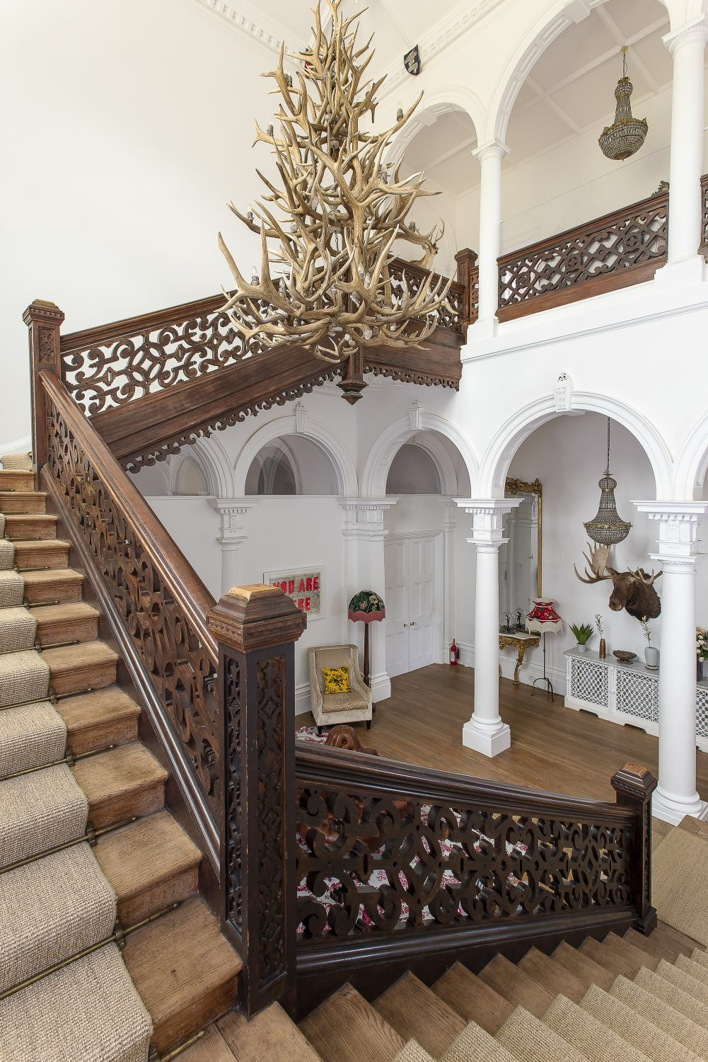 One of the most impressive spaces in the house is the double height inner hallway around which a carved wooden staircase floats
