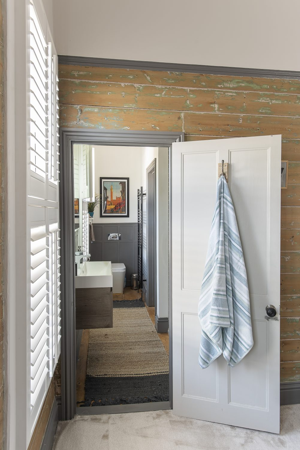 "Two bathrooms, one accessible from two doors, have been stylishly fitted with a contemporary bath and shower. One of the bedrooms retains its original wooden tongue and groove cladding. ""We started to sand it off,"" says Kelly, ""but liked the effect of leaving some of the green on the wood underneath."""