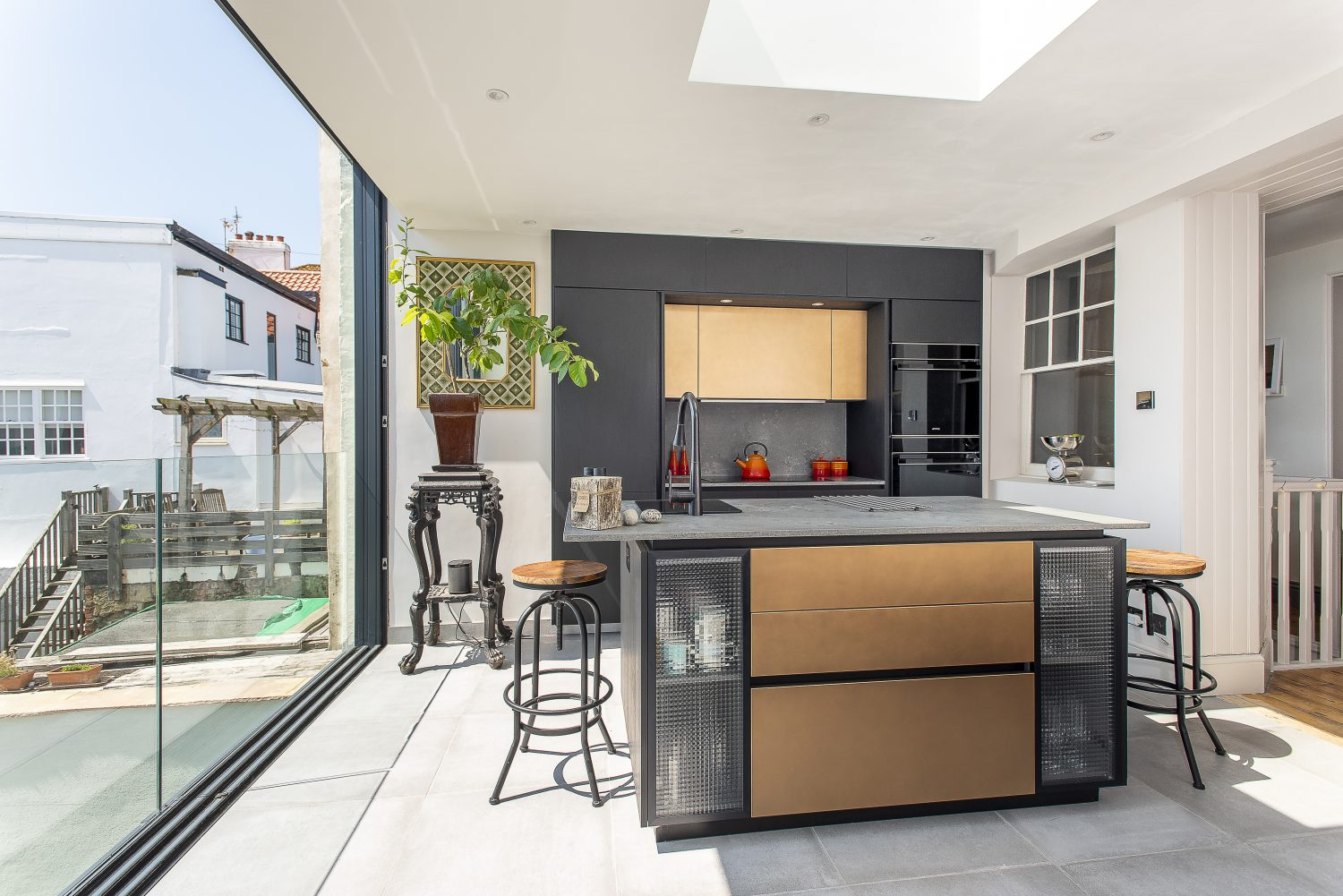 The Italian Doimo kitchen is streamlined and understated, serving as much as an entertaining space as a functional kitchen. The units are black wood and brass, with counter tops and splash backs in polished concrete and Smeg appliances