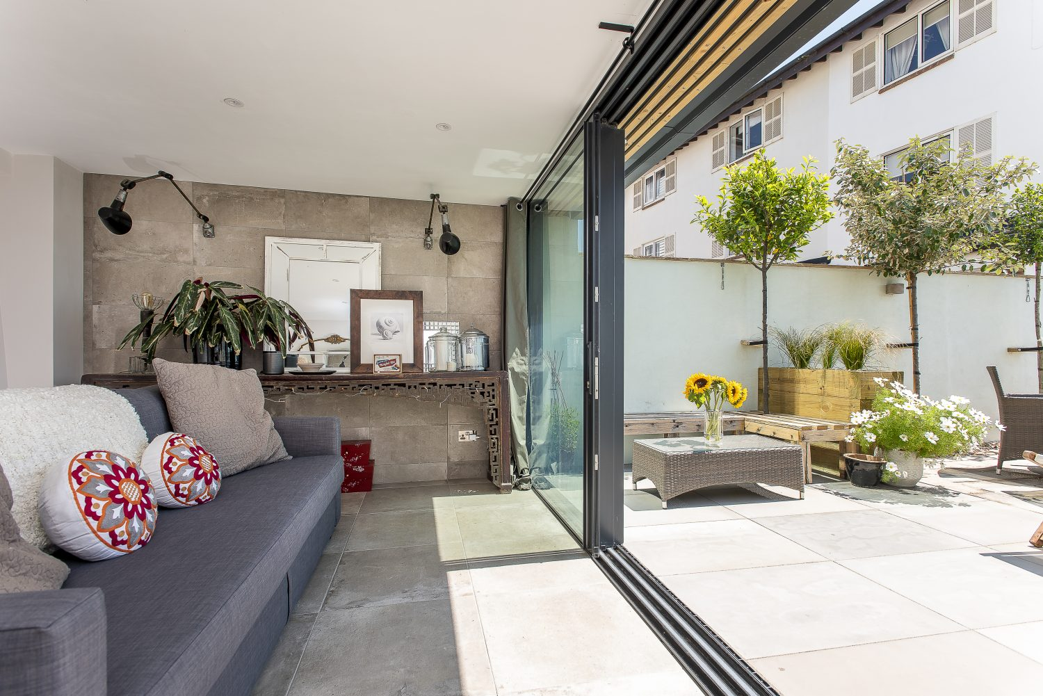 Sliding glass doors lead out from the mini-gym and garden room downstairs into the garden across porcelain paving, carefully chosen to blend the divide between the inside and the terrace