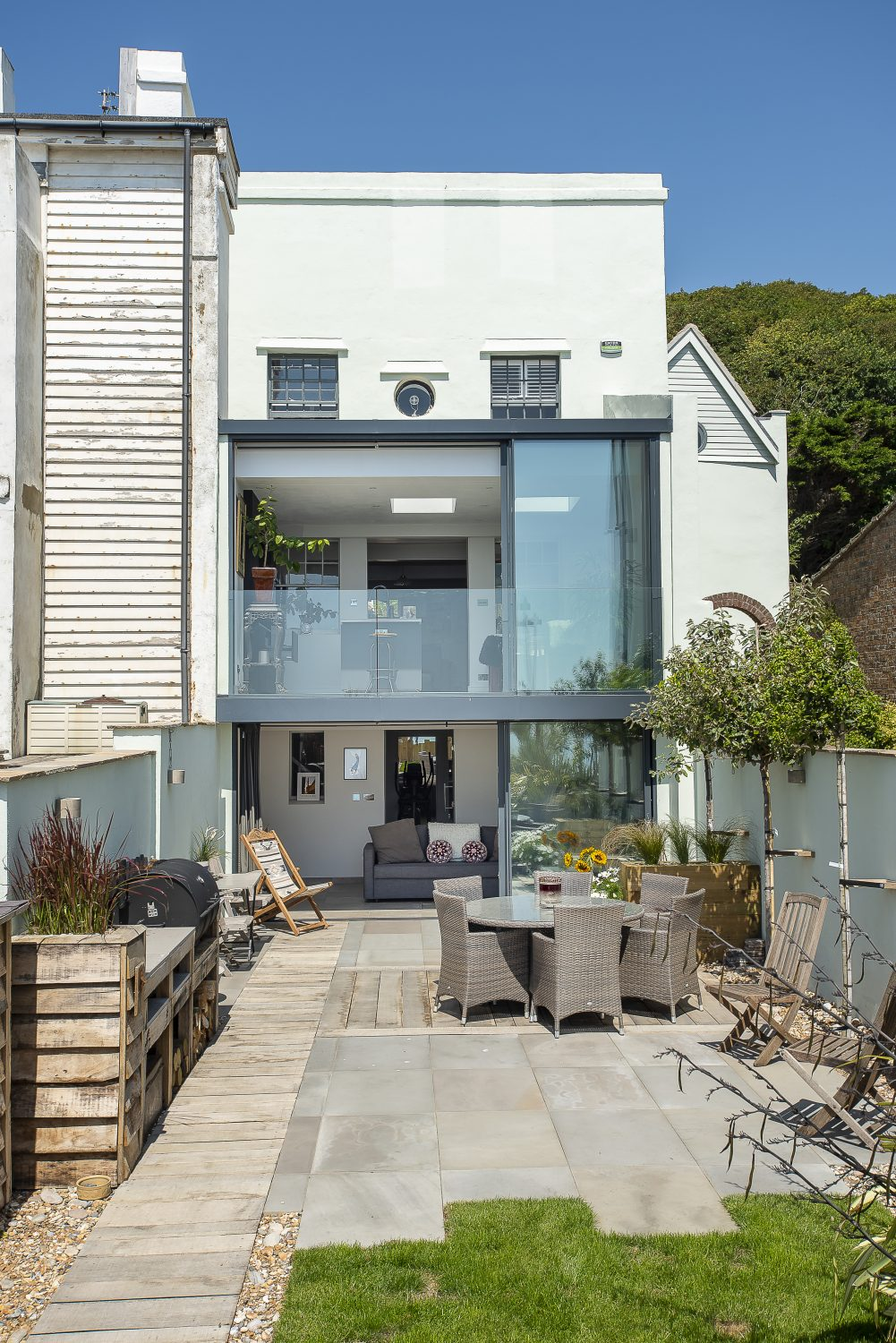 The precarious sun rooms were demolished and replaced with a contemporary double height extension, complete with virtually seamless sliding doors and a sheer glass balustrade