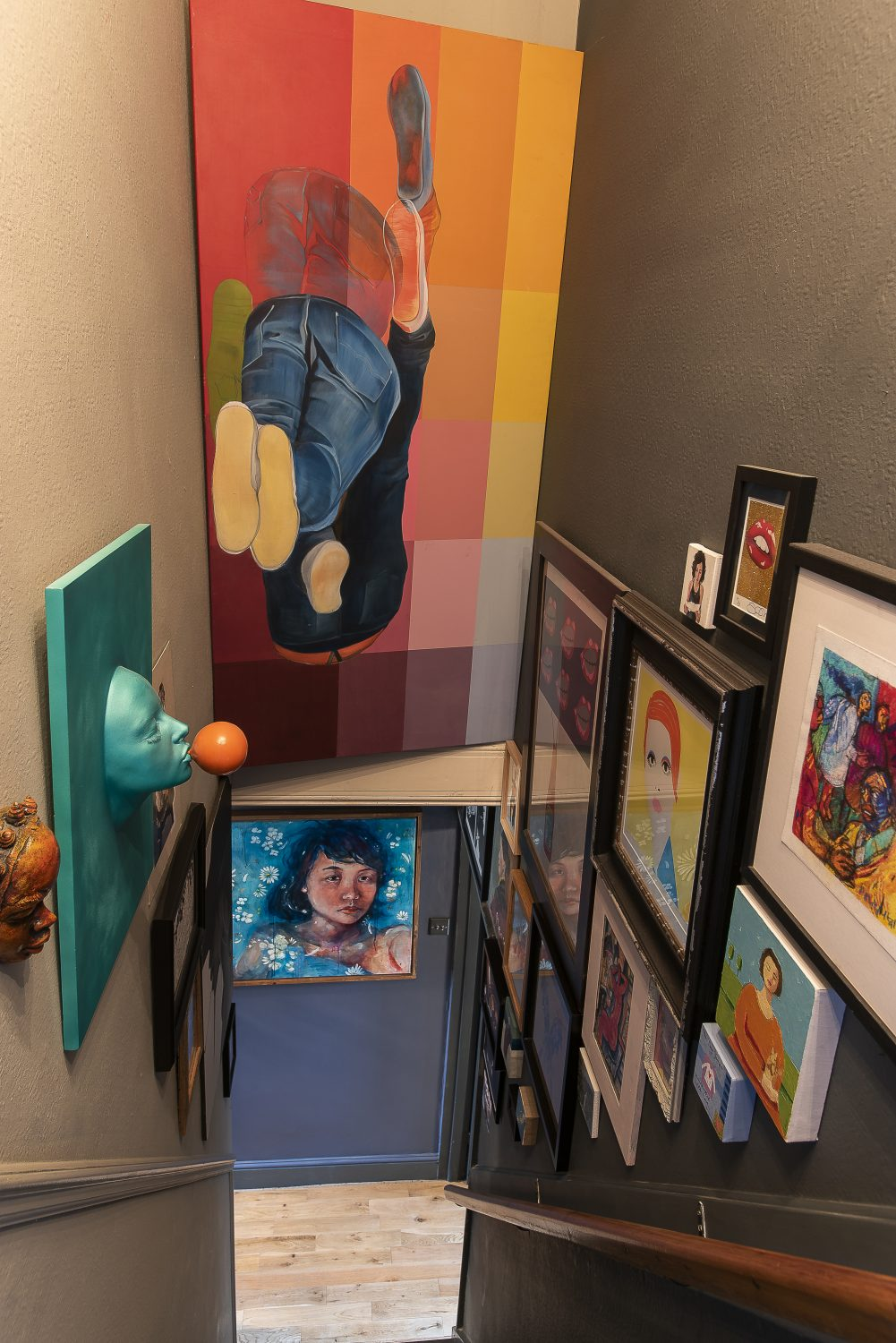 Prints, paintings and sculptures of assorted sizes cover the walls on either side of the staircase