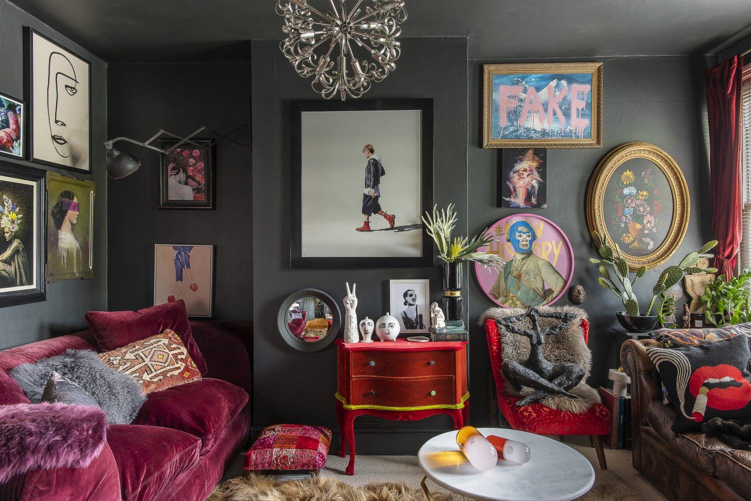 The almost black walls of the sitting room provide the perfect backdrop for Jaz's collection of artworks