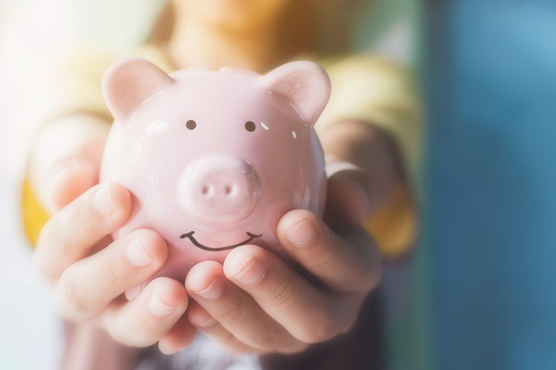 hands clutching piggy bank