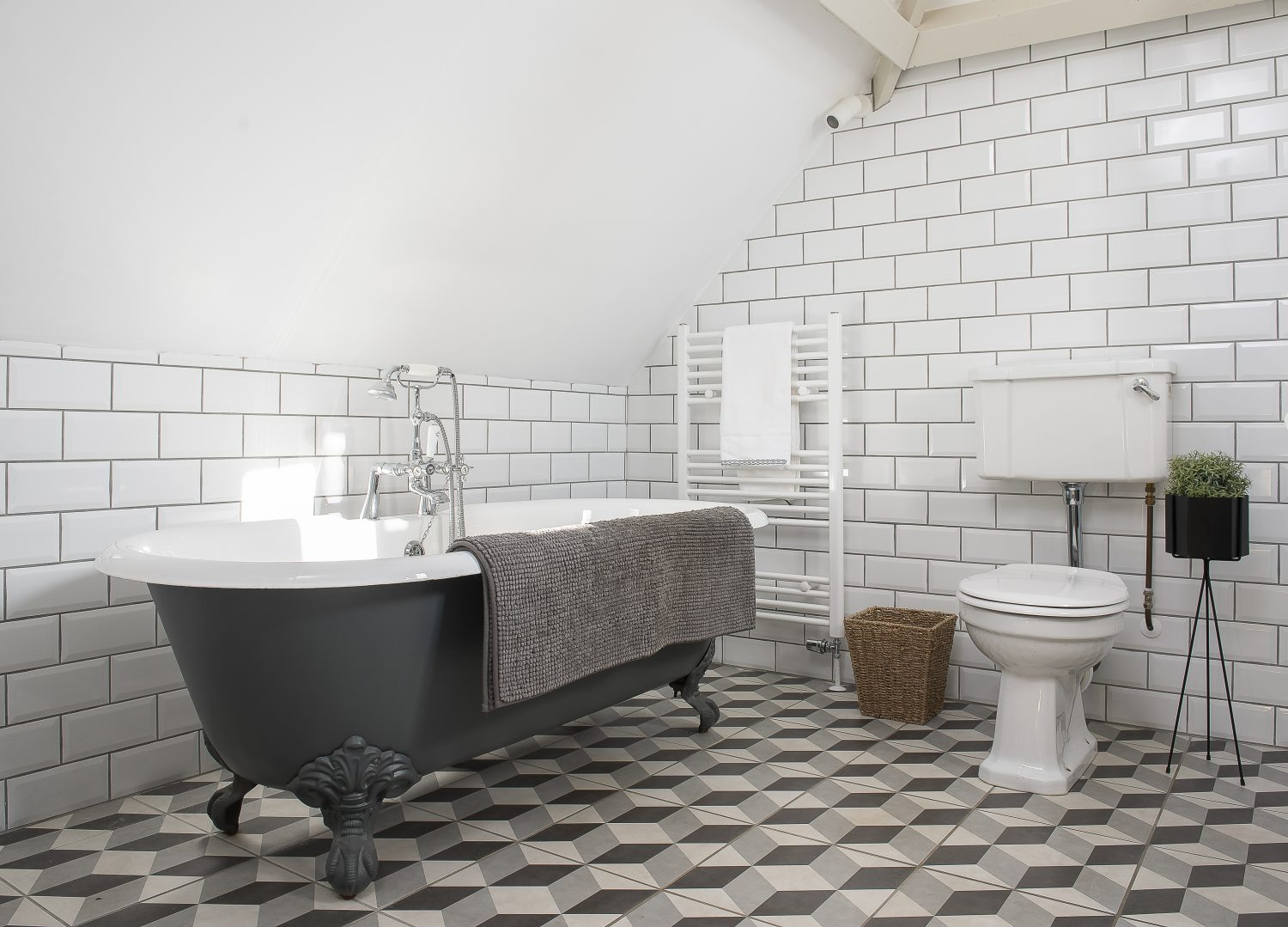 The master bathroom features beautiful geometric floor tiles that complement the matte black roll-top bath