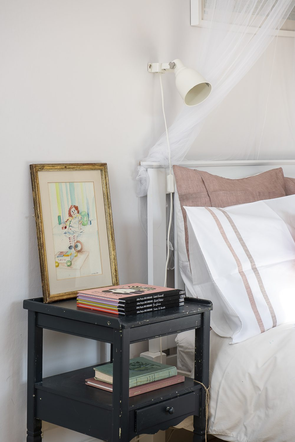 Toby and Megan's daughter's room has a built-in wardrobe and an original Arts and Crafts fireplace. Both are painted in Farrow & Ball's Brinjal, which works beautifully with the soft pinks in this delightful bedroom