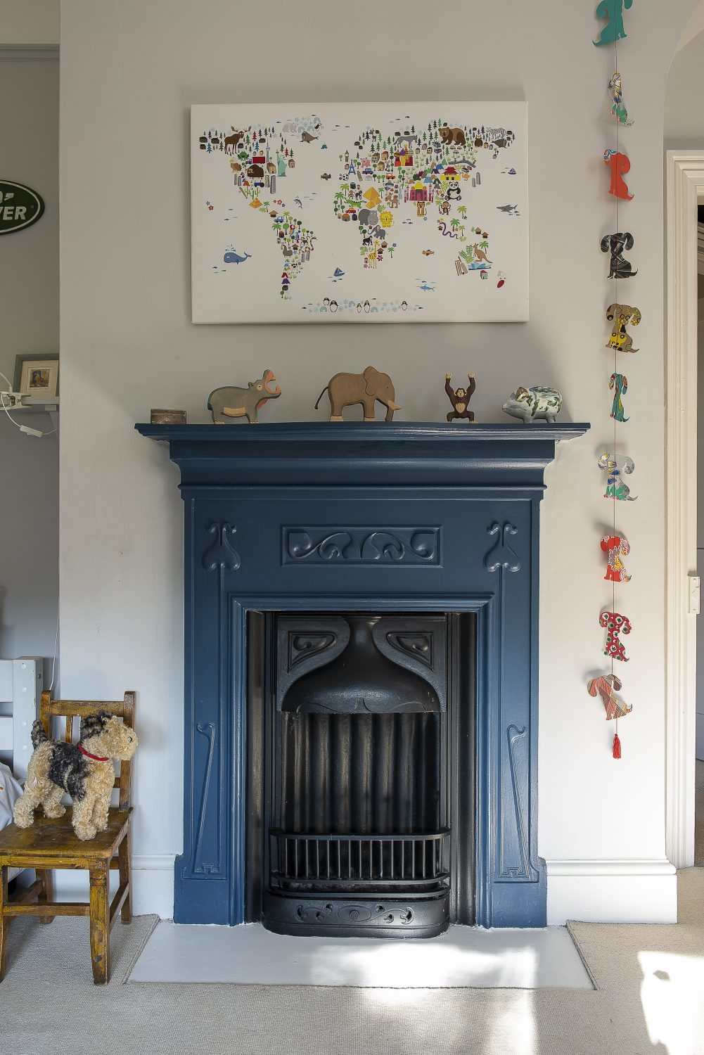 In the couple's son's room, Farrow & Ball's Stiffkey blue used for the fireplace works well with the red Anglepoise and yellow lampshade