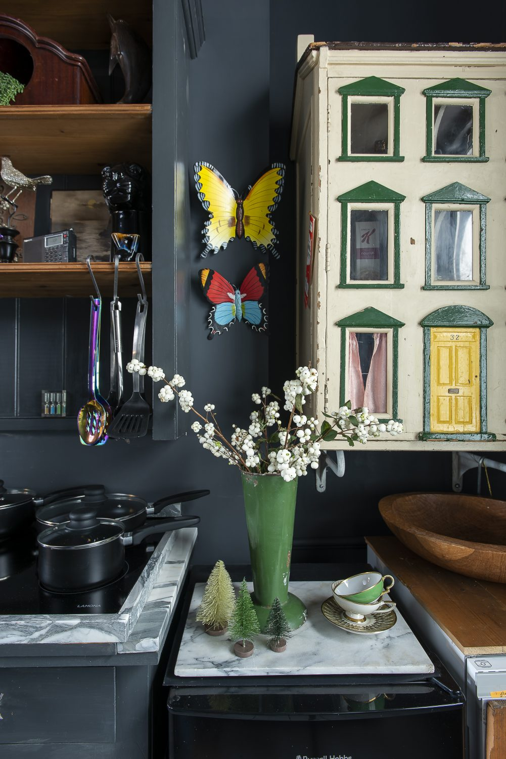 The dolls house, mounted on the wall, all the wallpaper still in place inside, makes a perfect storage space for kitchen cupboard staples