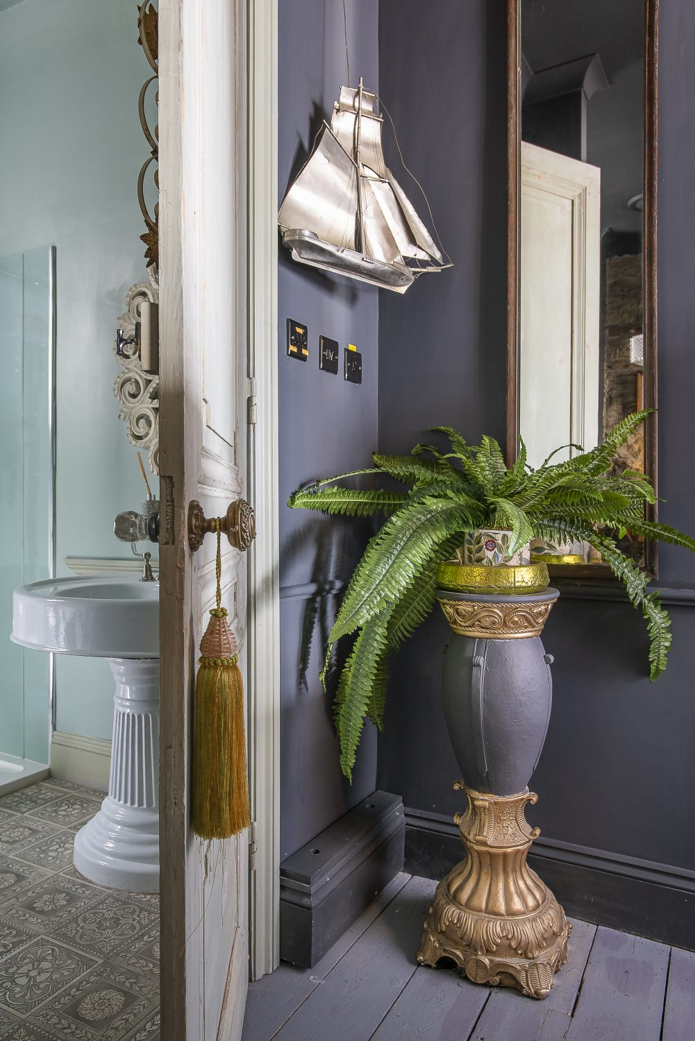 A chandelier from nationallighting.co.uk illuminates the sage green shower room, complete with an ornate pedestal basin