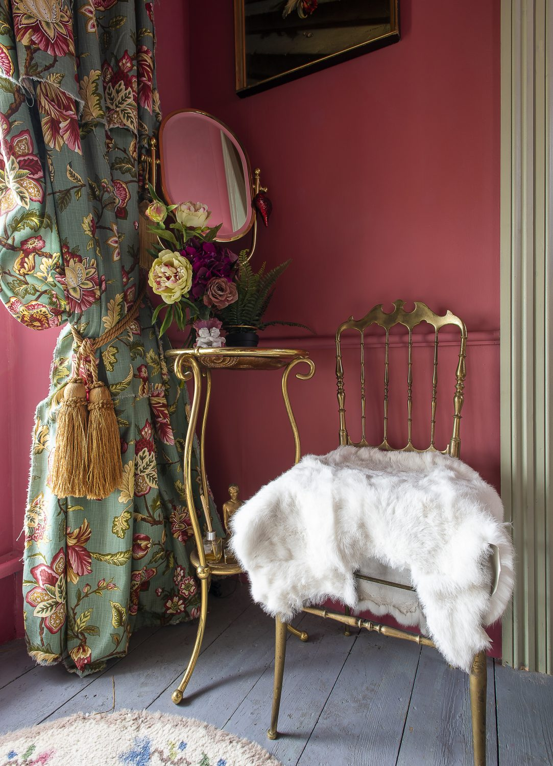 The wonderfully romantic bedroom is like a film set from the 1950s. The room is taken up almost entirely by a steel bed, made up with dramatic floral bed linen, from John Lewis, dressed with a floral counterpane and a purple fake fur throw