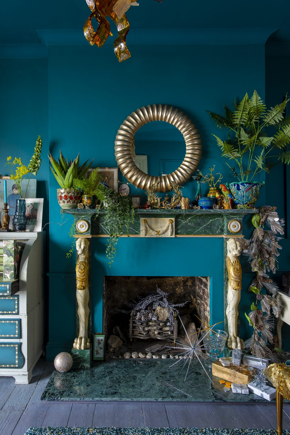 High ceilings and luxe touches of gold and marble add to a sense of grandeur, making the flat feel much larger than it really is. A round mirror, with ridges not dissimilar to an ammonite, sits above the mantelpiece adorned with an eclectic mix of ornaments, artworks and faux plants