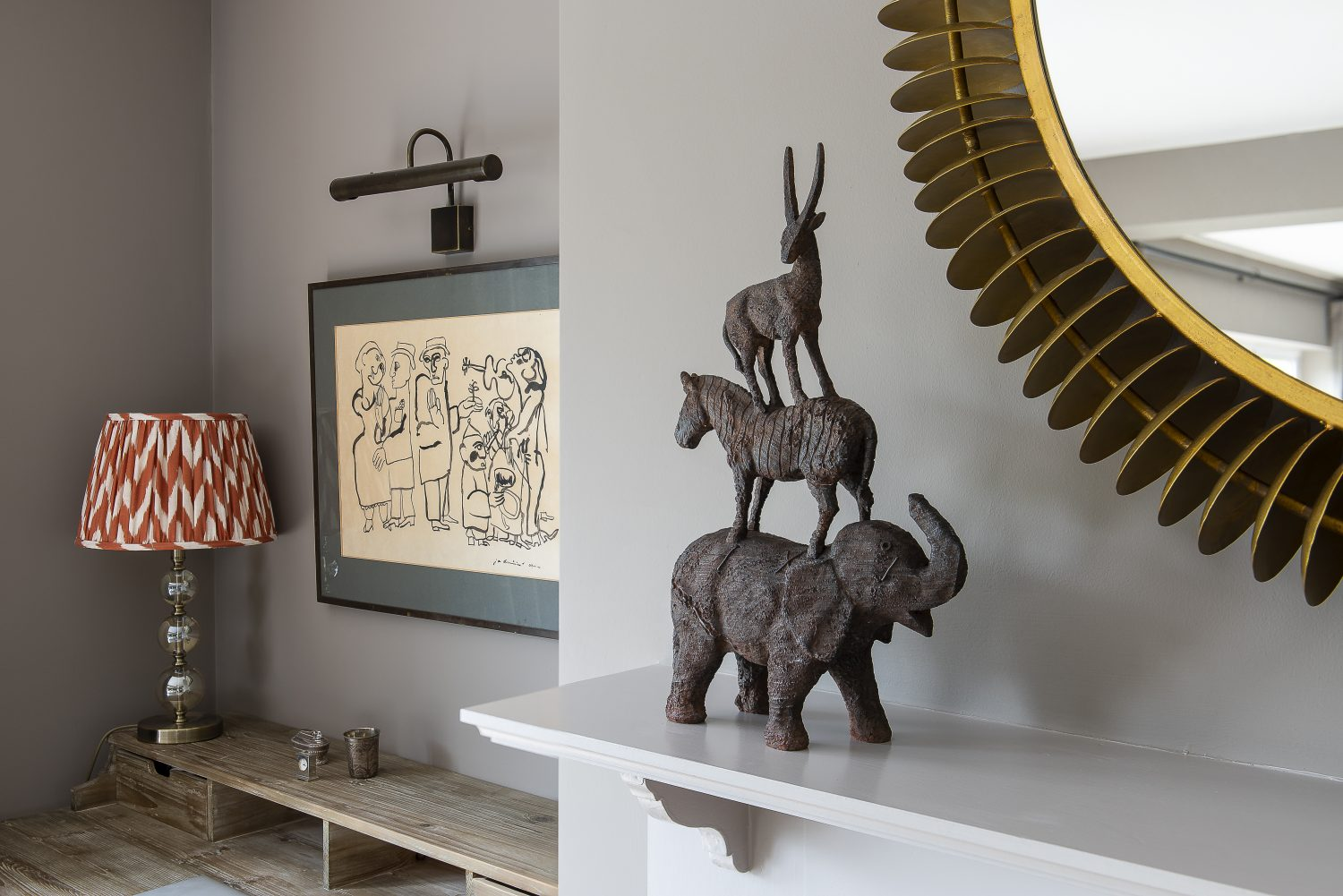 Cushions upholstered in prints by Rapture & Wright line up on the grey sofa that K and S already had when they moved in. A South African animal sculpture from Woodcocks in Tenterden sits on the mantelpiece below a gold mirror from Graham & Green in the children's area of the sitting room