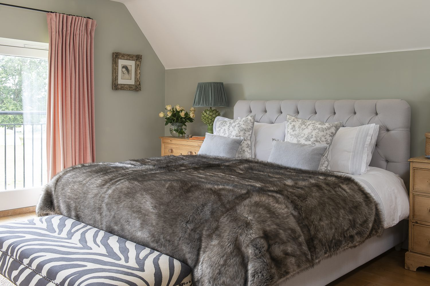 The faux fur throw and zebra print ottoman in the master bedroom are both Ally touches. The artichoke lamp is by Pooky