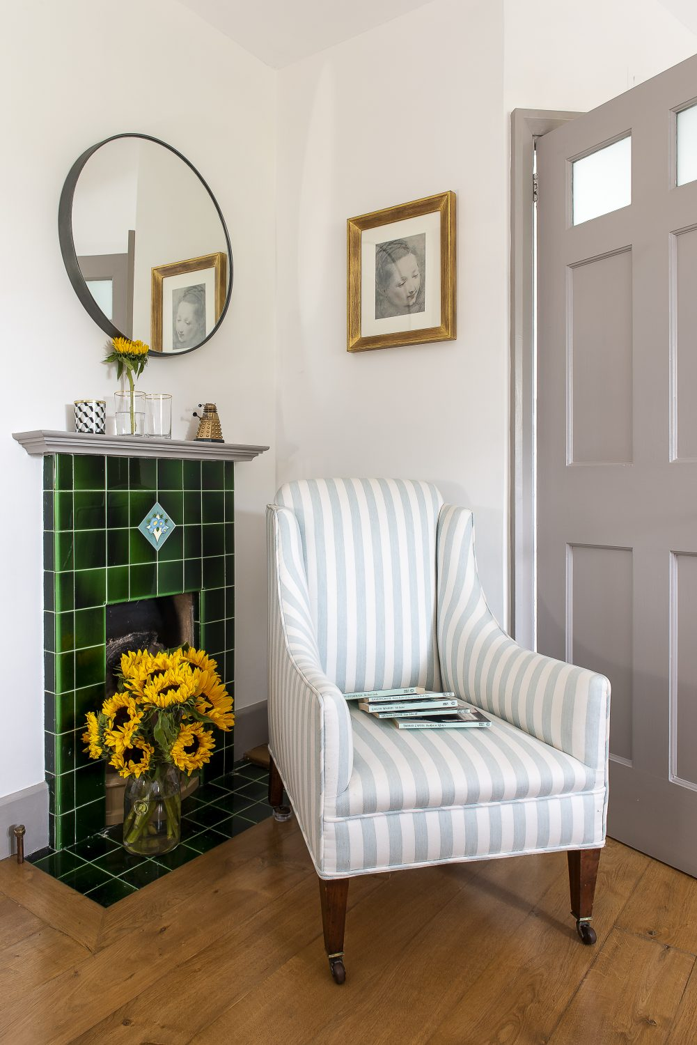 An antique chair sits comfortably by an original tiled fireplace in a guest bedroom