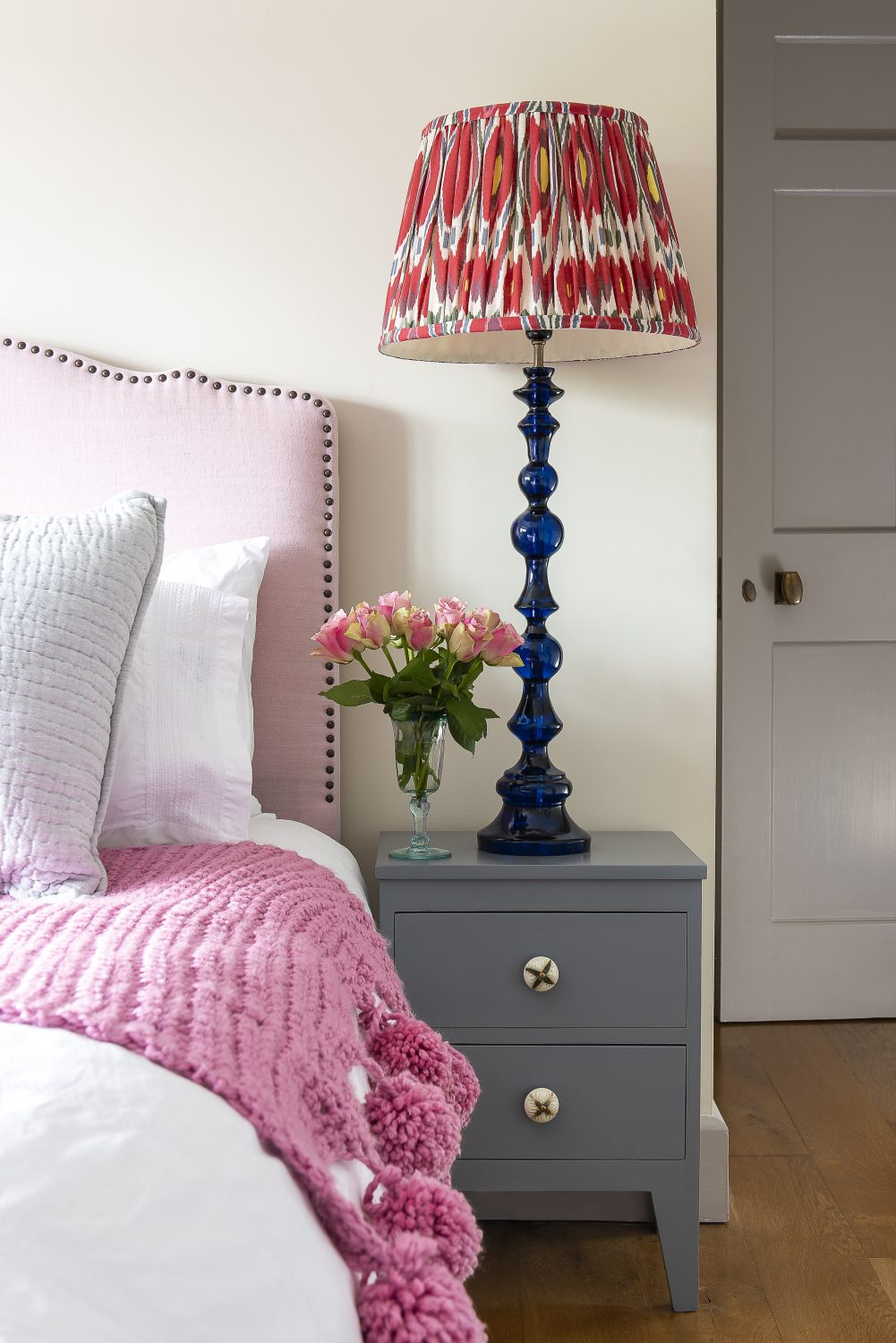 The 'Rose Room' follows a pink theme with lights by Pooky, an Ikea rug and a cosy woodburner in one corner