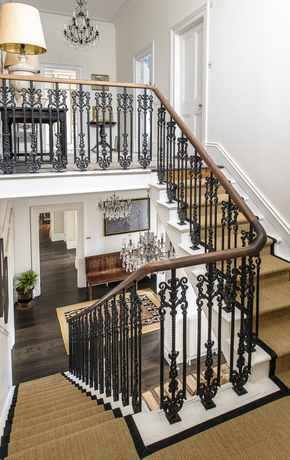 The magnificent wooden staircase has been carpeted in a natural jute