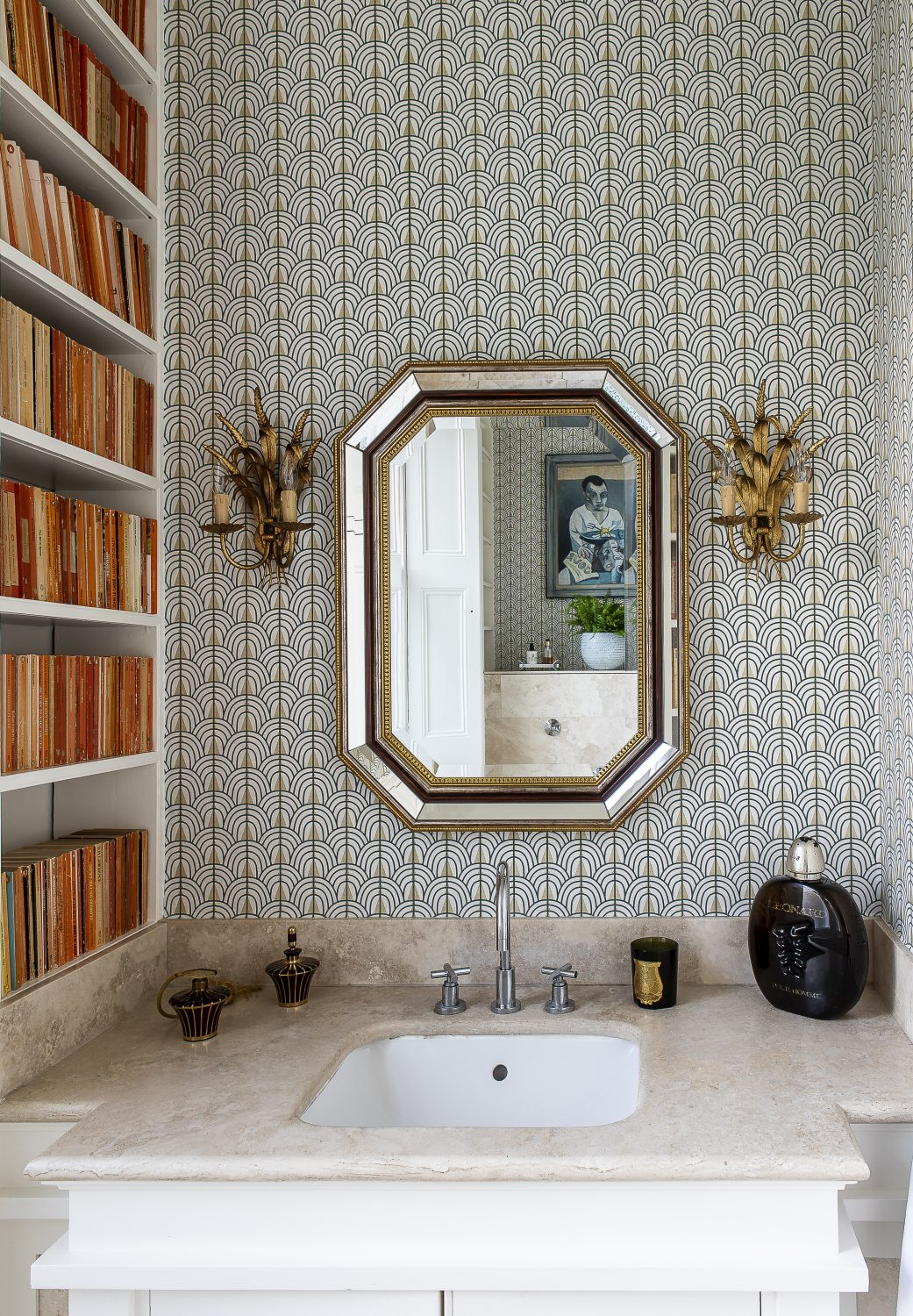 The downstairs loo has been decorated in a stylish contemporary geometric printed wallpaper. A bookcase is packed with Penguin classics, which Olya sourced from eBay. The marble sink is flanked by two wheatsheaf lighting sconces that sit either side of an antique mirror