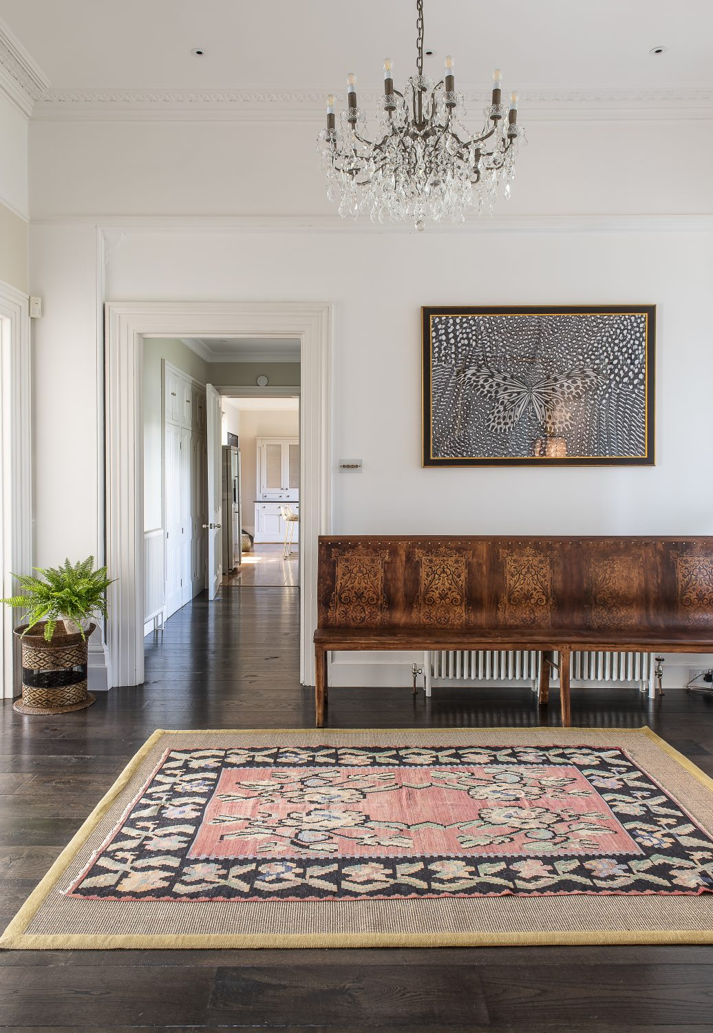 Olya has kept the walls in the entrance hall neutral and the floors stained dark, which has allowed the geometric patterns of the Sahara Tuareg reed and leather rug, as well as the pieces of antique furniture and paintings, to shine