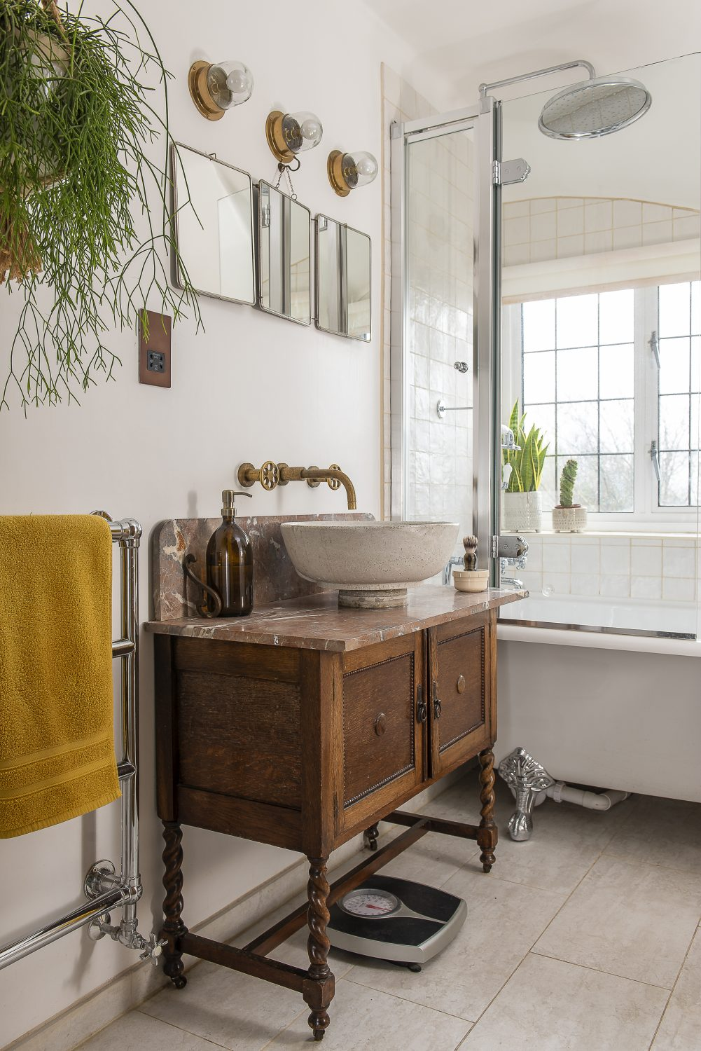 Justine has turned the small bathroom into a hotel-standard space, with a vintage free-standing vanity unit and brushed brass taps that perfectly reflect the aesthetic in the rest of the house. More houseplants lend a vibrant feel