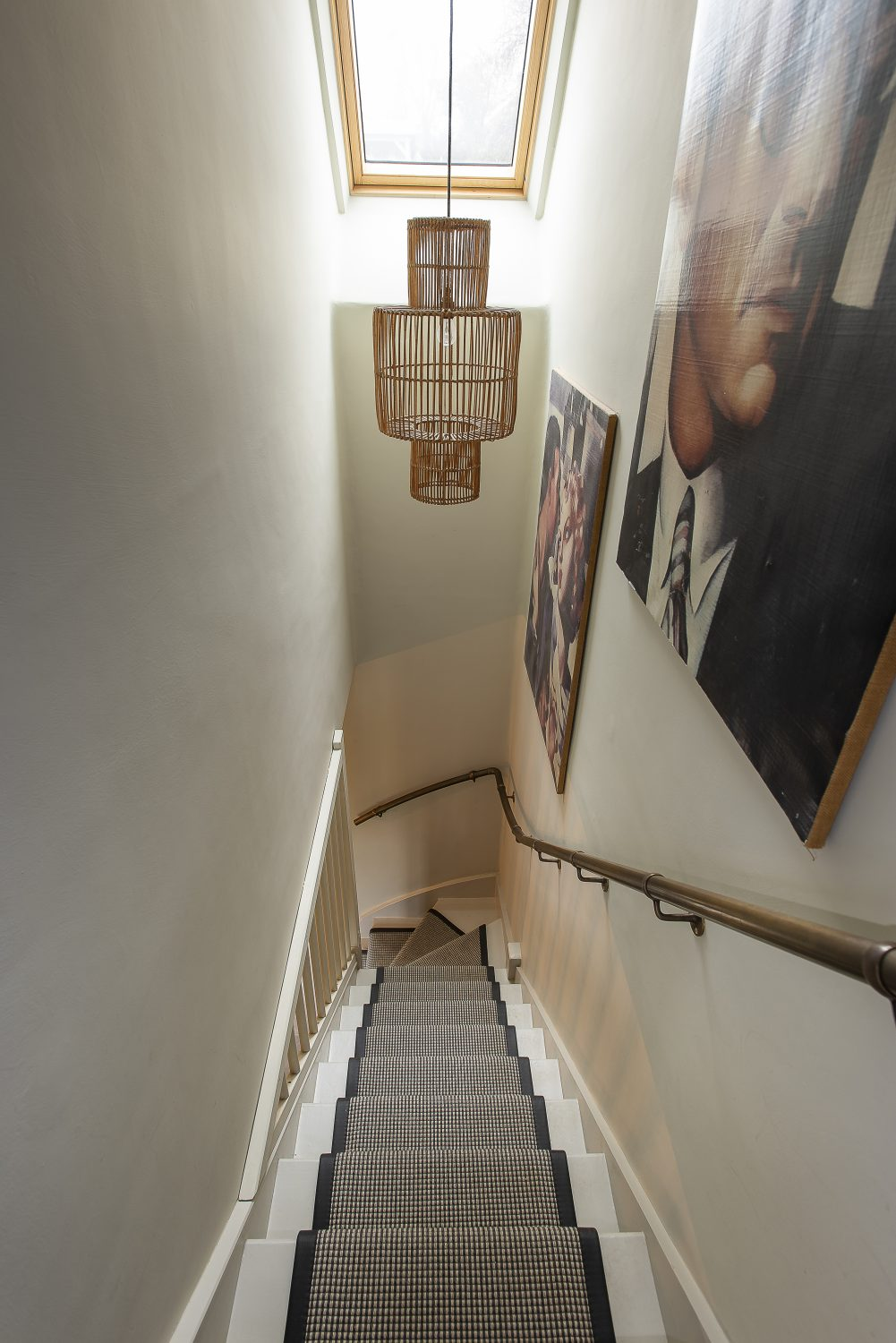 Large-scale artworks line the stairway walls. The sisal-style carpet continues the natural theme