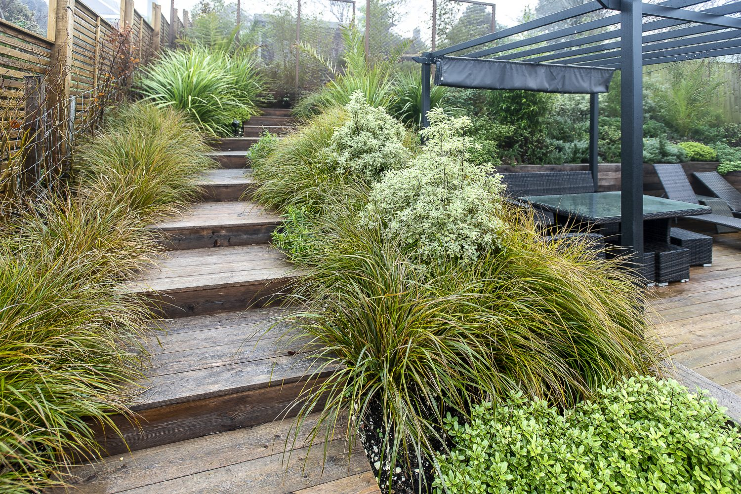 Evergreen planting schemes and wide terraces designed by Tina Vallis lead up towards the summerhouse