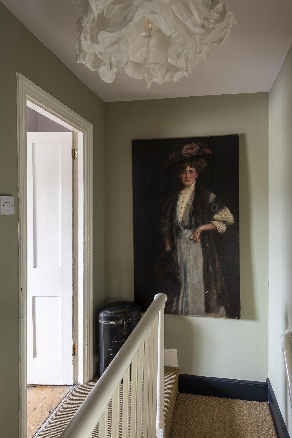 A large portrait of Lillie Langtry by Richard Jack hangs on the landing below another striking Ikea paper lampshade