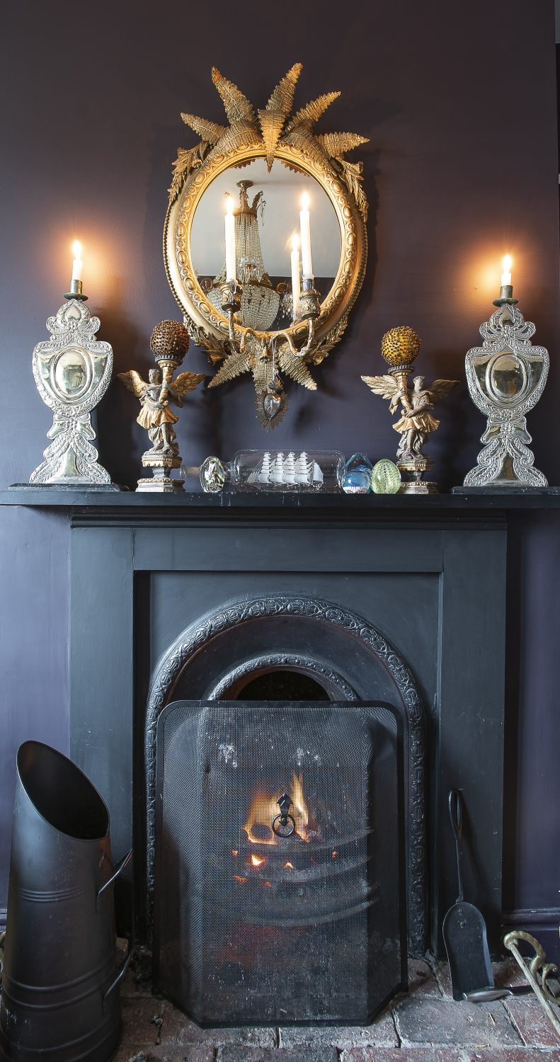 The gilded mirror over the fireplace with ferns, candles in place, came from Norman Road in St Leonards