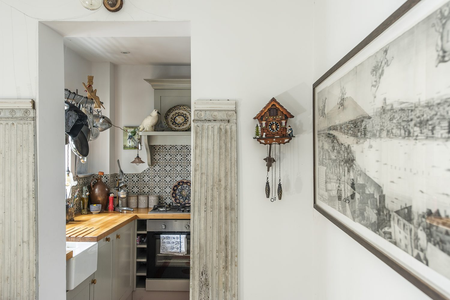 There are pillars on either side of the kitchen entrance – where Sally plans to add a theatrical curtain, currently drawn on the wall with pencil – and three working cuckoo clocks
