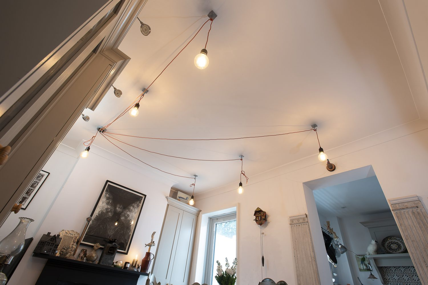 In the dining room, varied lengths of bright orange corded cable stretch out from the central ceiling rose with bare bulbs hanging from hooks