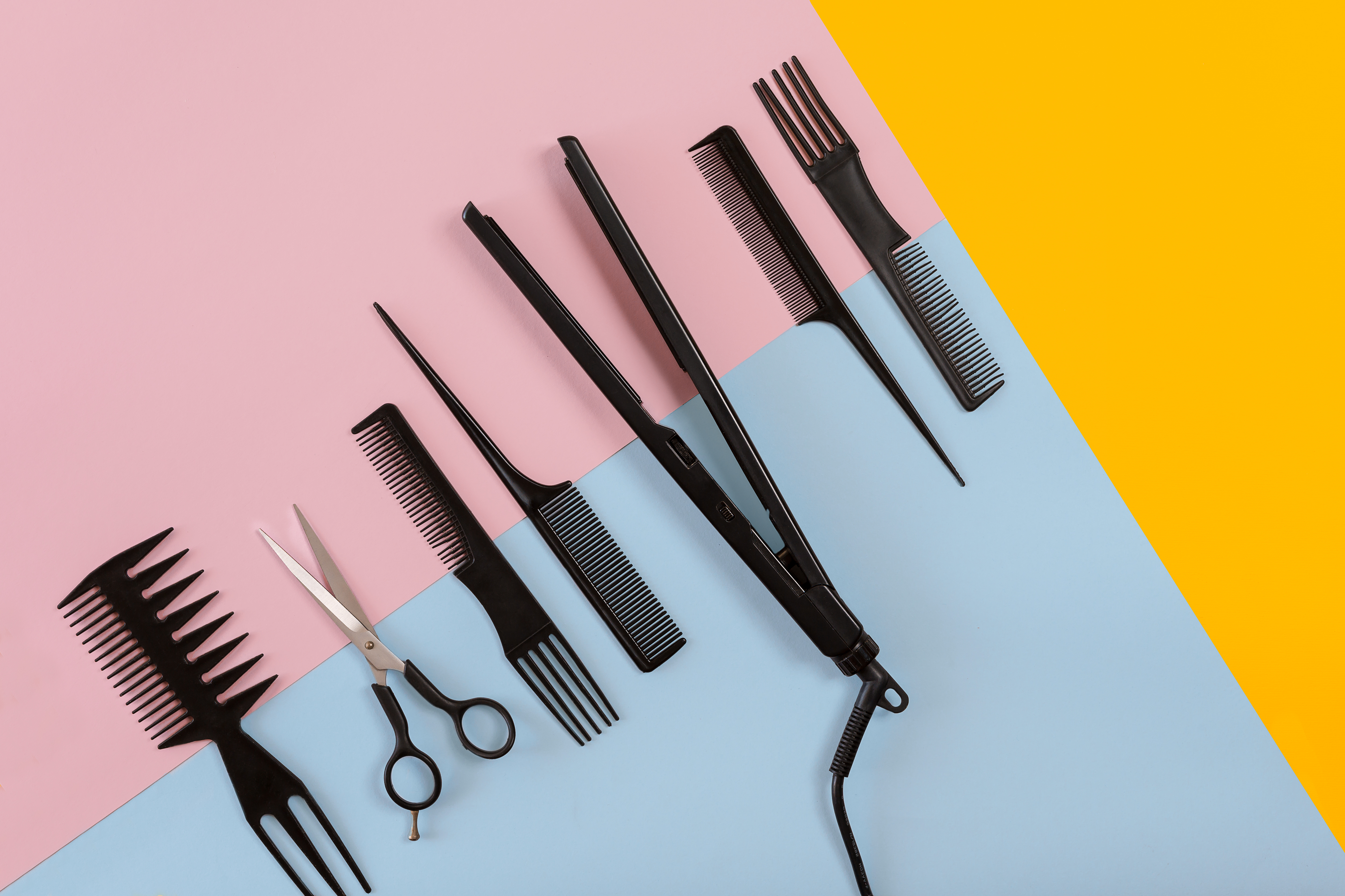Various hair styling devices on the color blue, yellow, pink paper background, top view